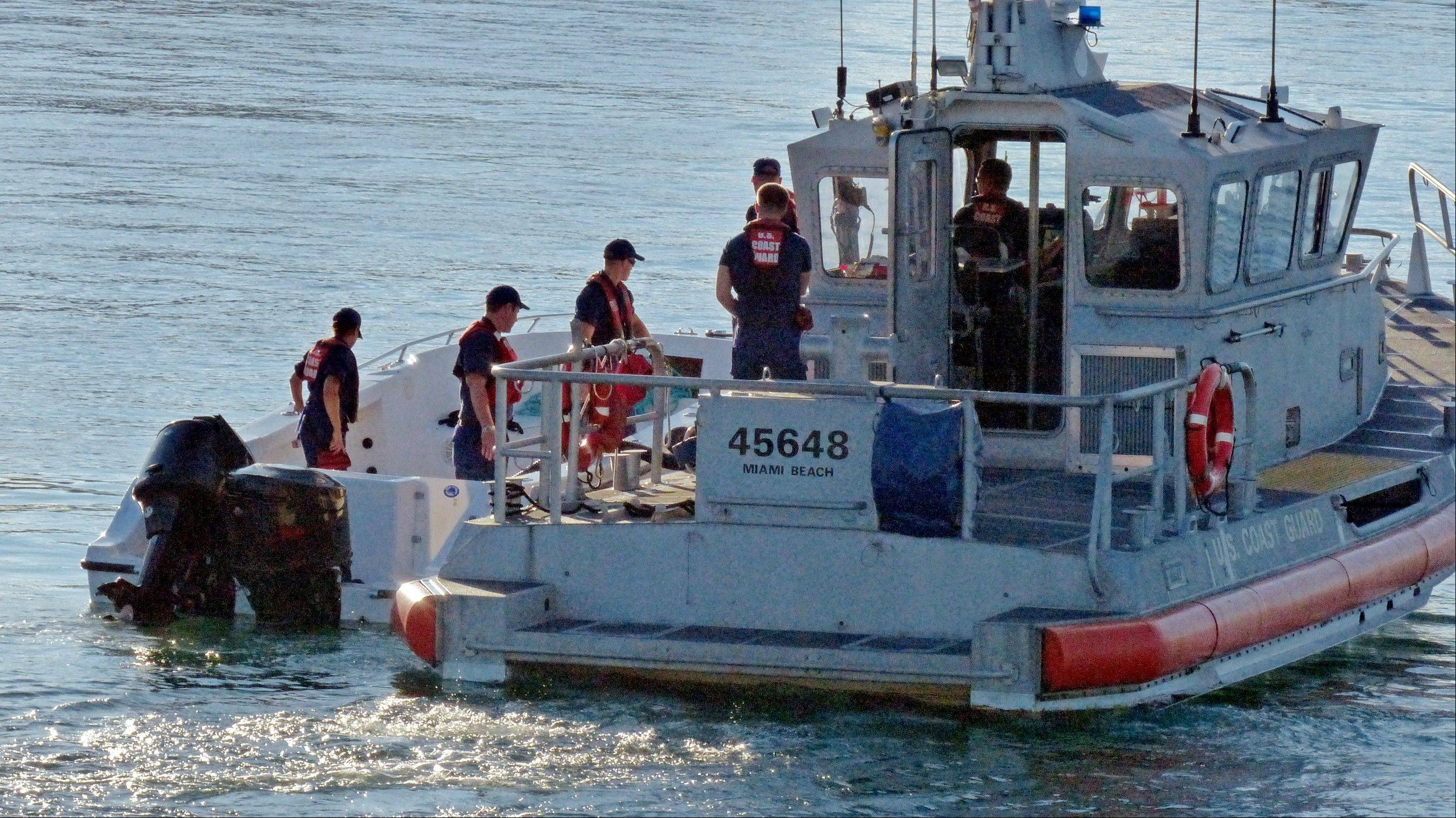 U.S. Coast Guard personnel investigate a vessel with a missing center console that capsized near Miami, Wednesday, Oct. 16, 2013. Four women died and 10 other people were taken into custody after the boat with more than a dozen people aboard, including Haitian and Jamaican nationals, capsized.