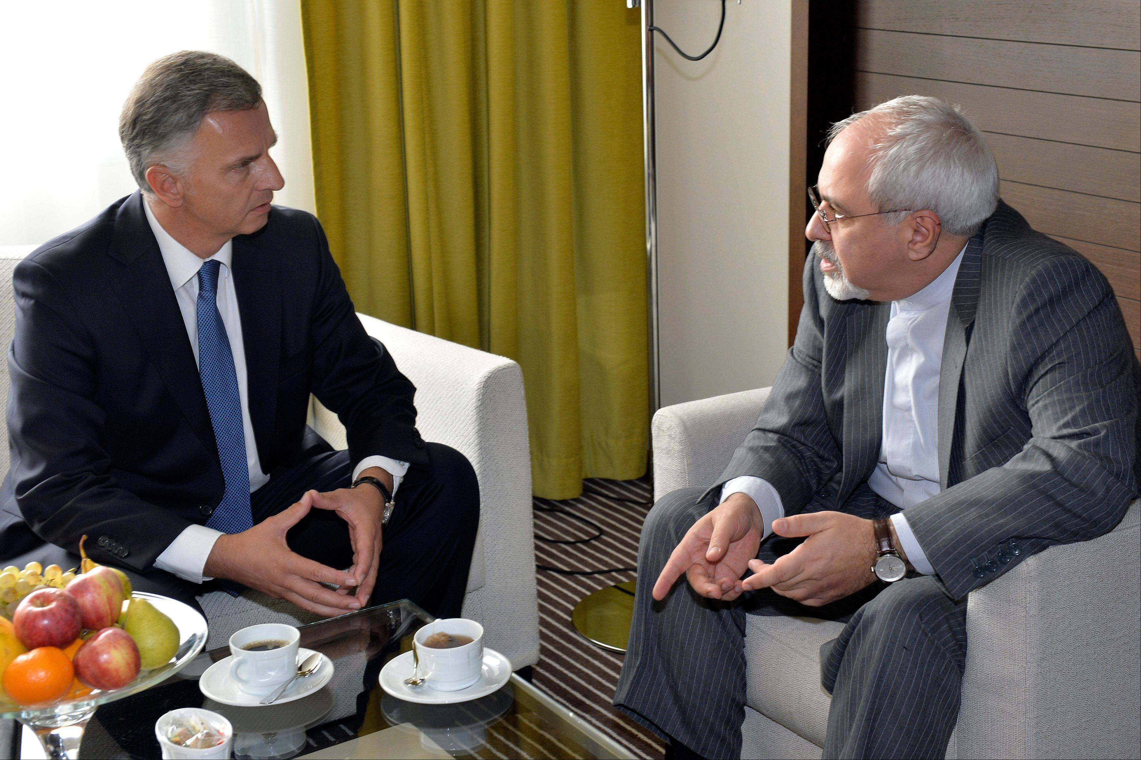 Switzerland�s Foreign Minister Didier Burkhalter, left, speaks with Iranian Foreign Minister Mohammad Javad Zarif, right, during a meeting besides of the two days of closed-door nuclear talks in Geneva, Switzerland, Wednesday.