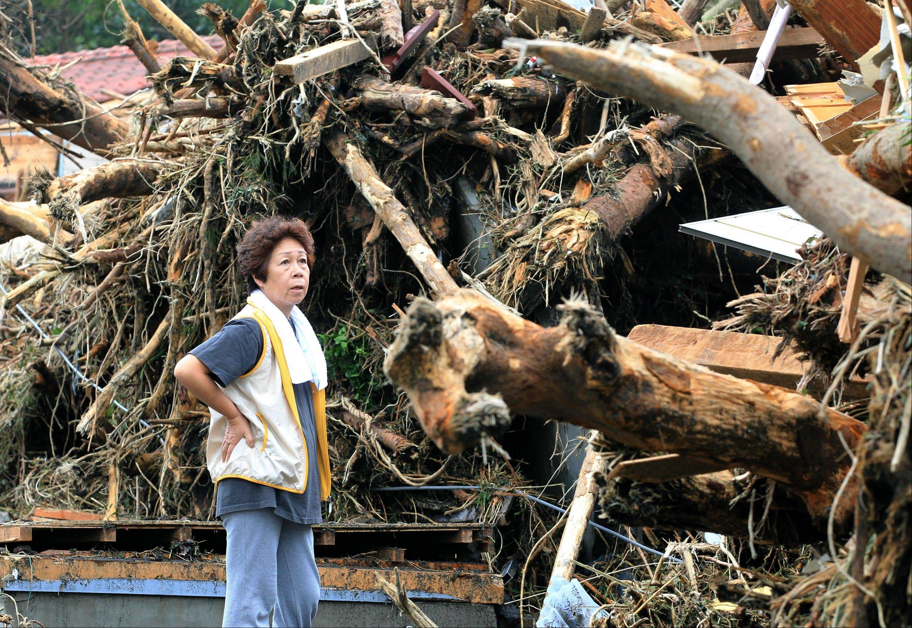 A woman looks at the aftermath of landslides in the rubble of smashed houses in Oshima after a powerful typhoon hit Izu Oshima island, about 75 miles south of Tokyo Wednesday morning, Oct. 16, 2013. Typhoon Wipha triggered landslides and caused multiple deaths on the Japanese island, before sweeping up the country's east coast, grounding hundreds of flights and paralyzing public transportation in Tokyo during Wednesday morning's rush hour.