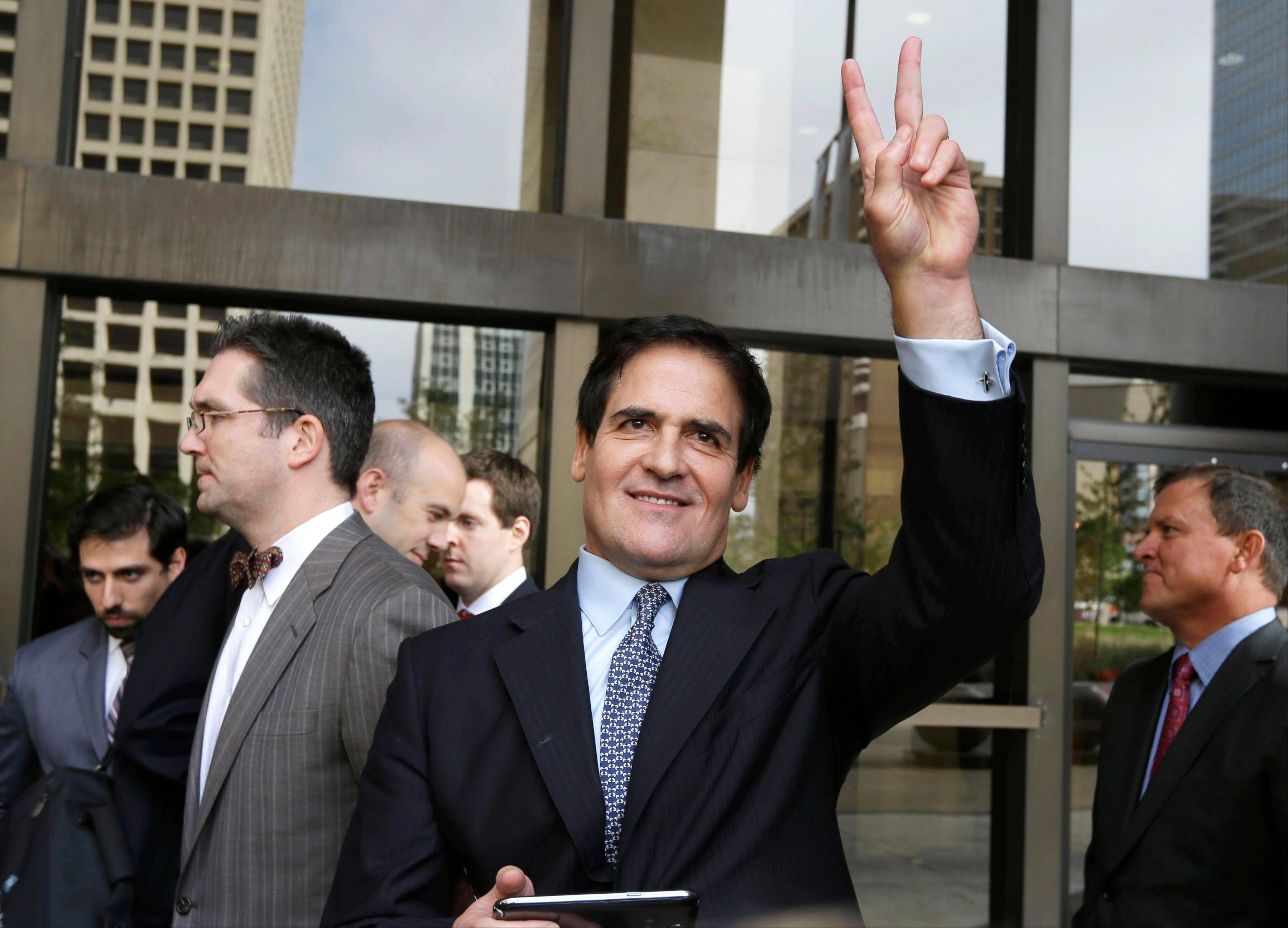 Mavericks team owner Mark Cuban gives a victory sign outside the federal courthouse Wednesday after the verdict in his insider trading trial in Dallas.