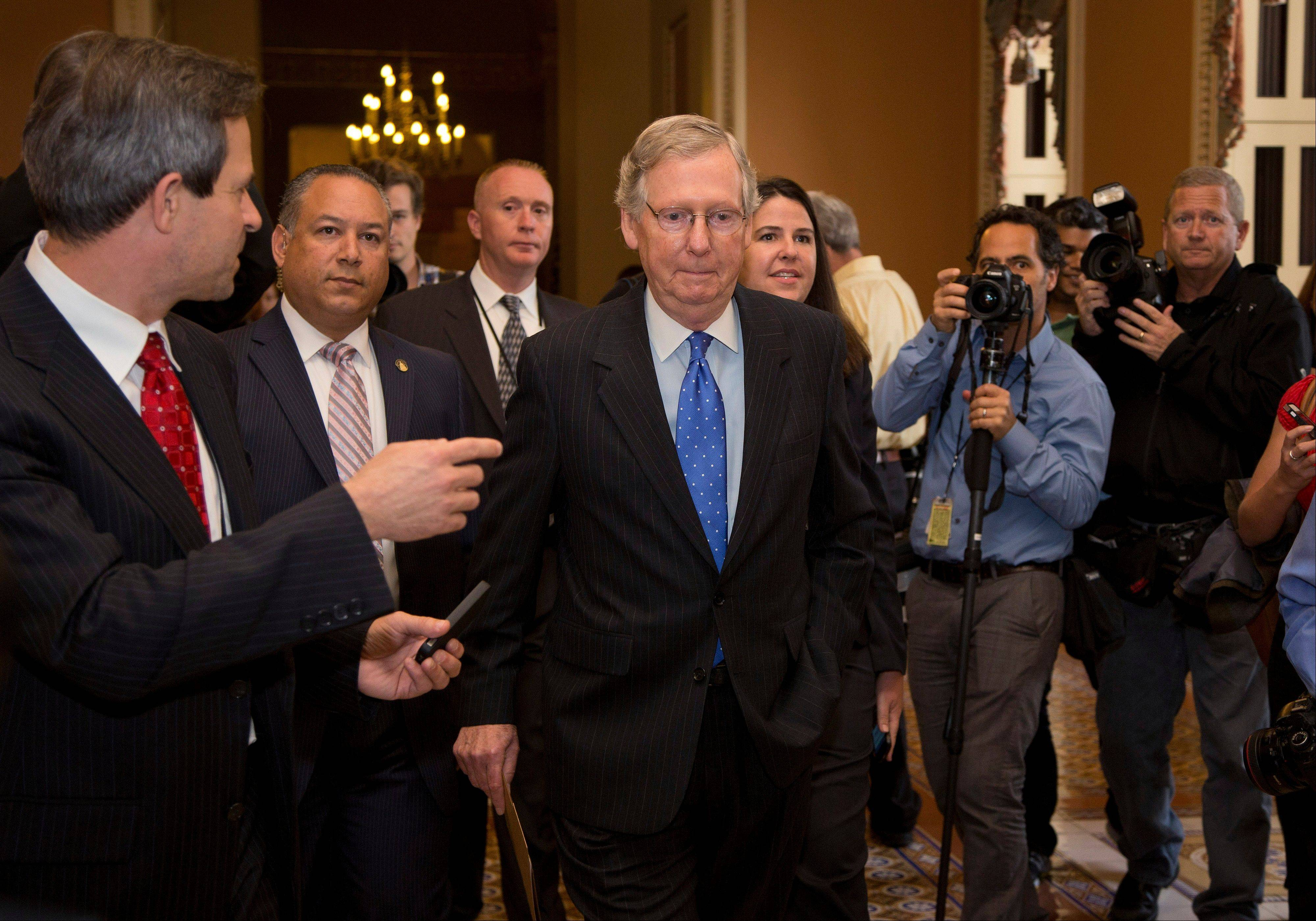 Senate Minority Leader Sen. Mitch McConnell, R-Ky., walks to the Senate floor after agreeing to the framework of a deal to avoid default and reopen the government on Capitol Hill on Wednesday, Oct. 16, 2013 in Washington.