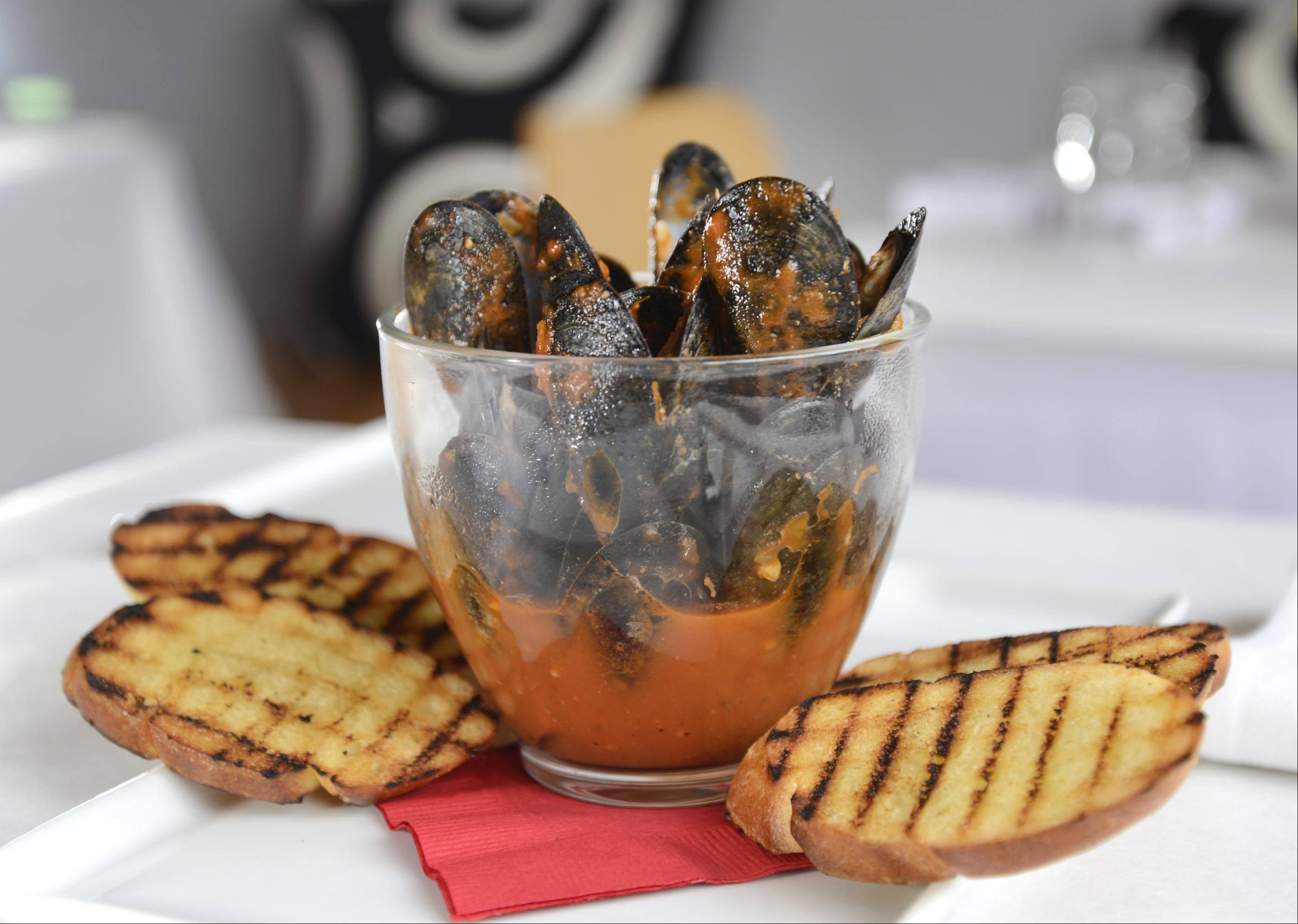 Al mejillon (mussels) served with Spanish chorizo and tequila sauce is an example of the fusion cuisine created at Altiro in Geneva.