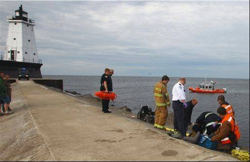 Ludington, Mich., emergency personnel respond to a call of a woman in a wheelchair falling off the north breakwater and into Lake Michigan near Ludington's North Breakwater Lighthouse Tuesday.