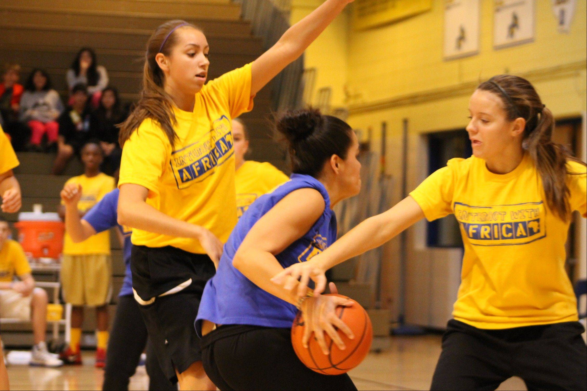 Wheeling High School's Deanna Kuzmanic, left and Elizabeth Smith, right, defend the basket in last year's Hoops for Africa game.