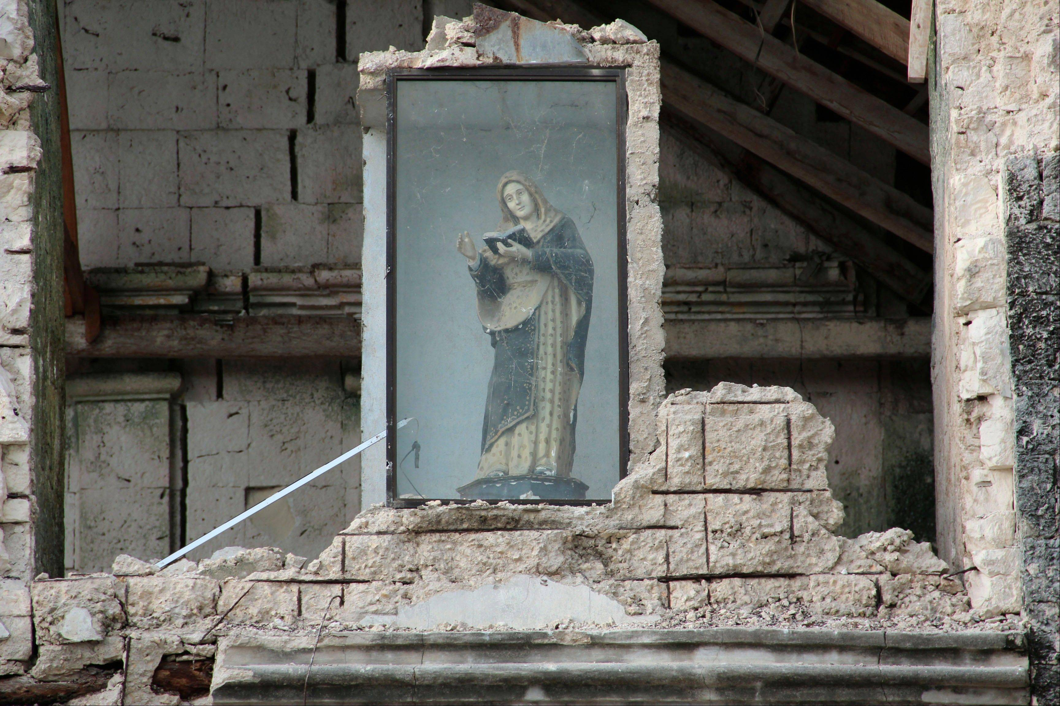 A religious icon remains encased amid the rubble in Bohol province in central Philippines Wednesday, Oct. 16, 2013, a day after a 7.2-magnitude quake hit Bohol and Cebu provinces. The quake that struck the central Philippines and killed more than a hundred people also dealt a serious blow to the region's historical and religious legacy by heavily damaging a dozen or more churches, some of them hundreds of years old.