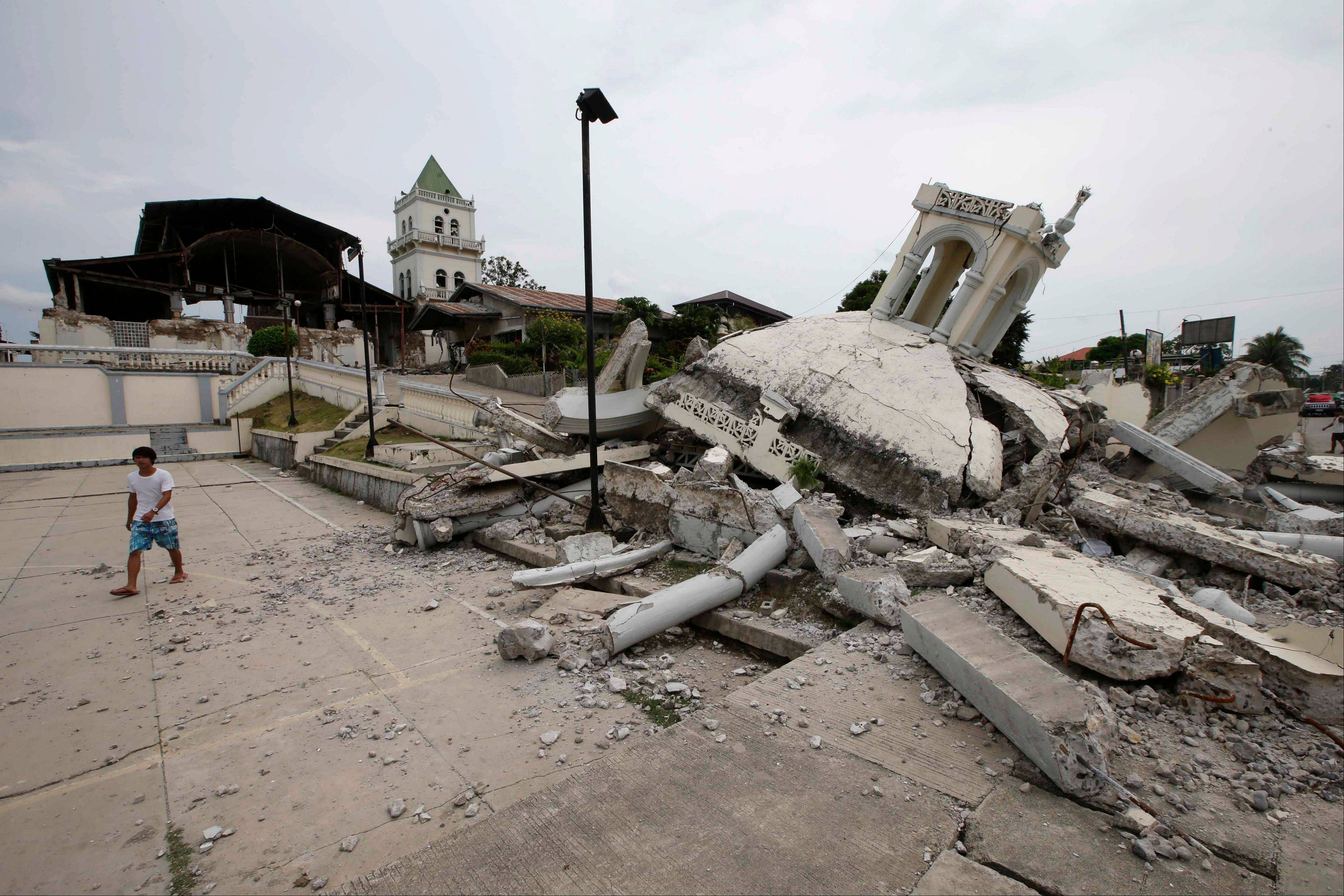 A boy walks away from the rubble of San Isidro de Labrador church in central Philippines. A 7.2-magnitude quake hit Bohol and Cebu provinces Tuesday damaging churches, buildings and homes and causing multiple deaths across the central region.