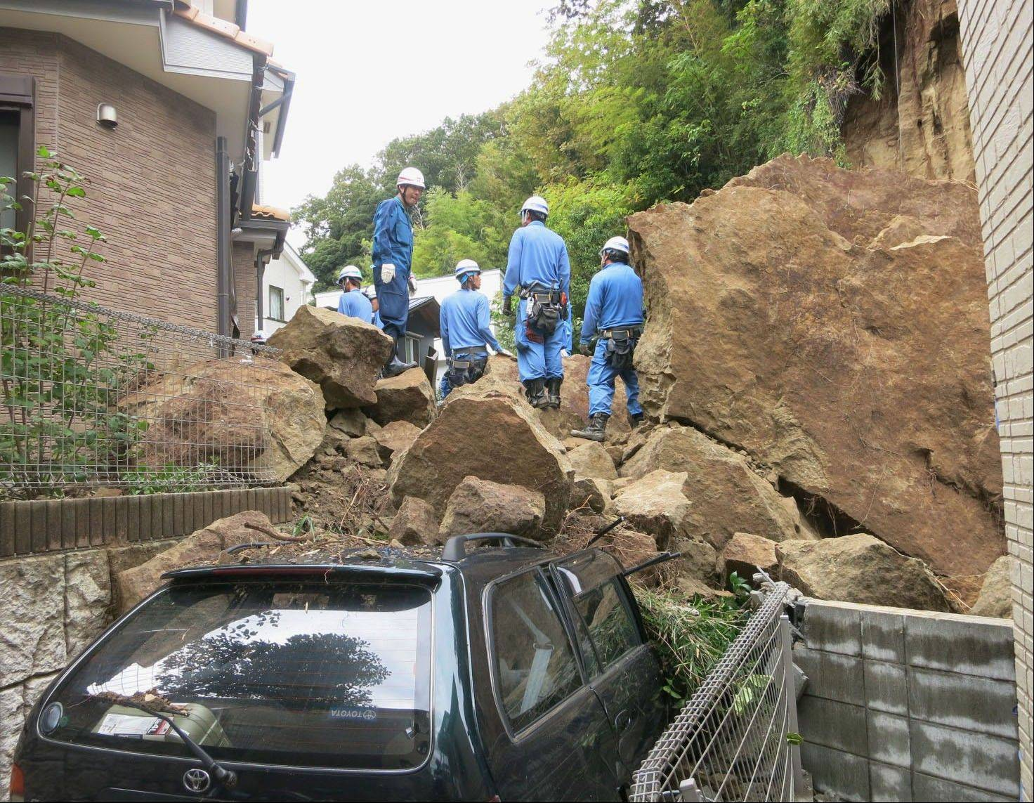 Firefighters stand on rocks fallen from a cliff over a garage and a road in a residential area in Kamakura, southwest of Tokyo, after a powerful typhoon hit Japan's metropolitan area Wednesday morning, Oct. 16, 2013.