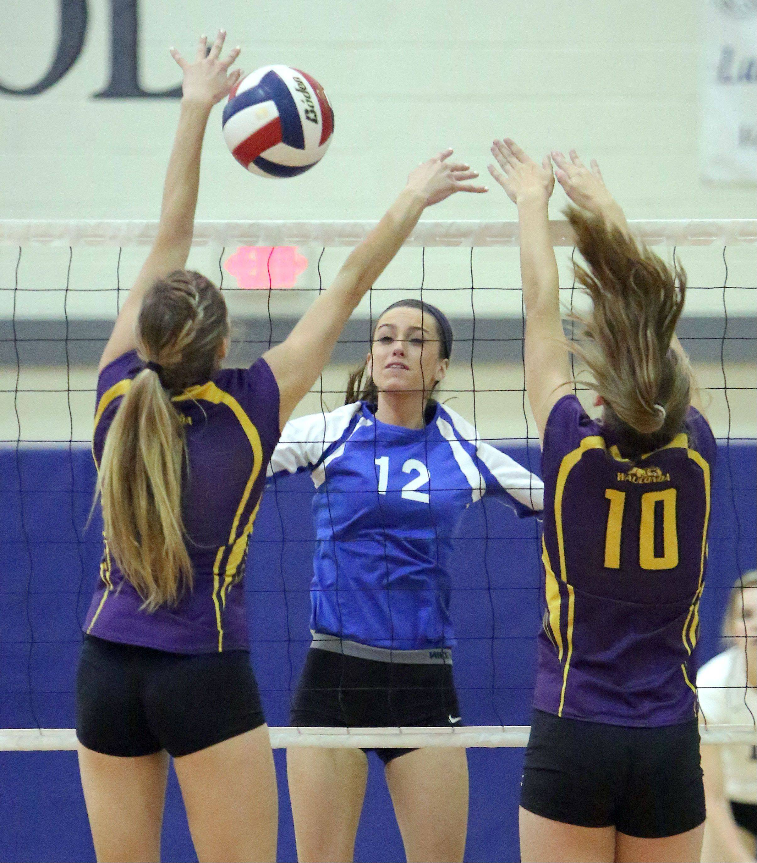 Lakes' Haley Halberg spikes one at Wauconda's Susan Karhoff, left, and Haley Redmann on Wednesday night at Lakes.