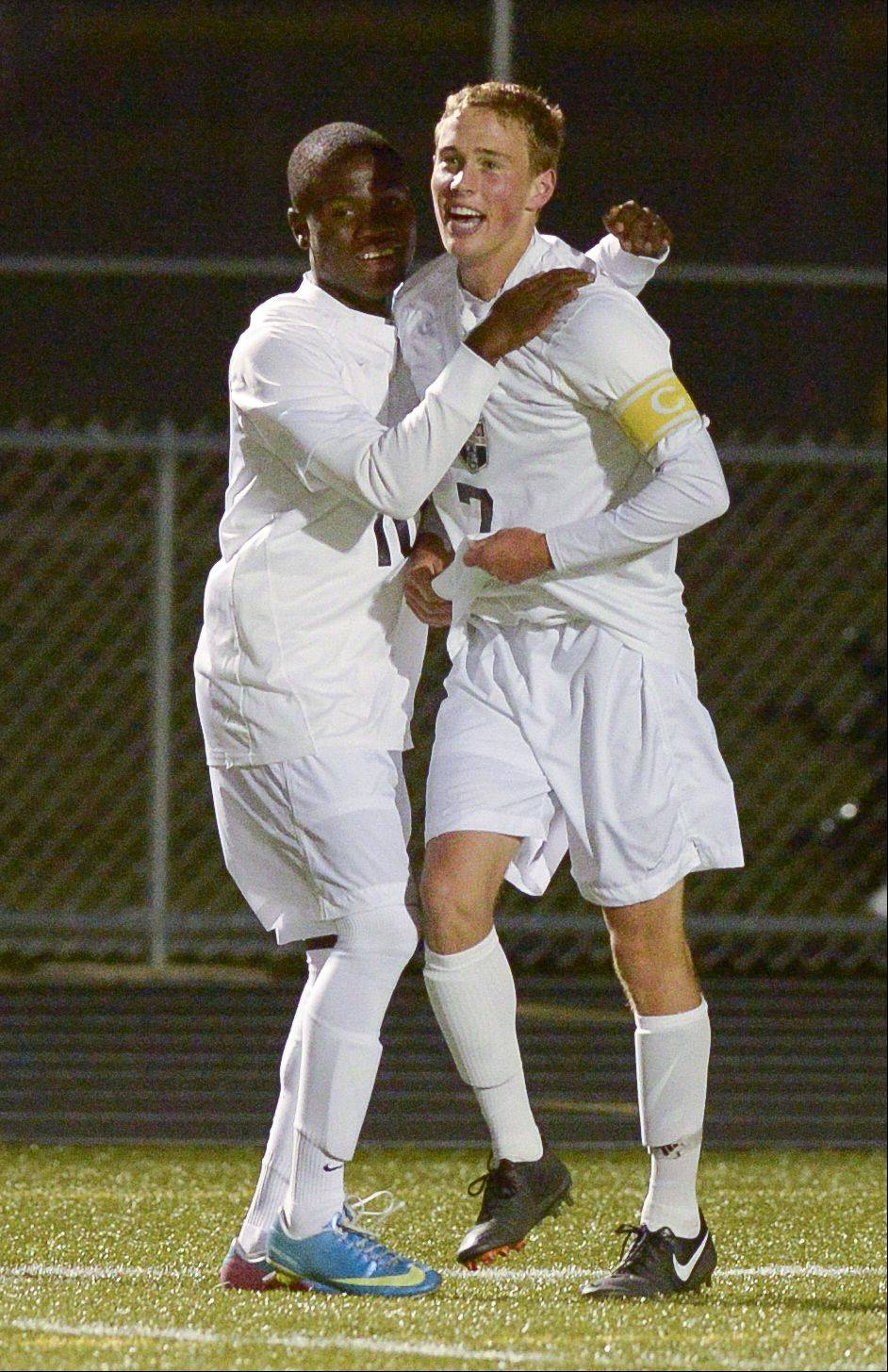 Metea Valley's Chris Freeman, left, gives his teammate Dakota Rowsey a hug after he scored a goal in the first half of play against St. Charles East during boys soccer at home Wednesday.