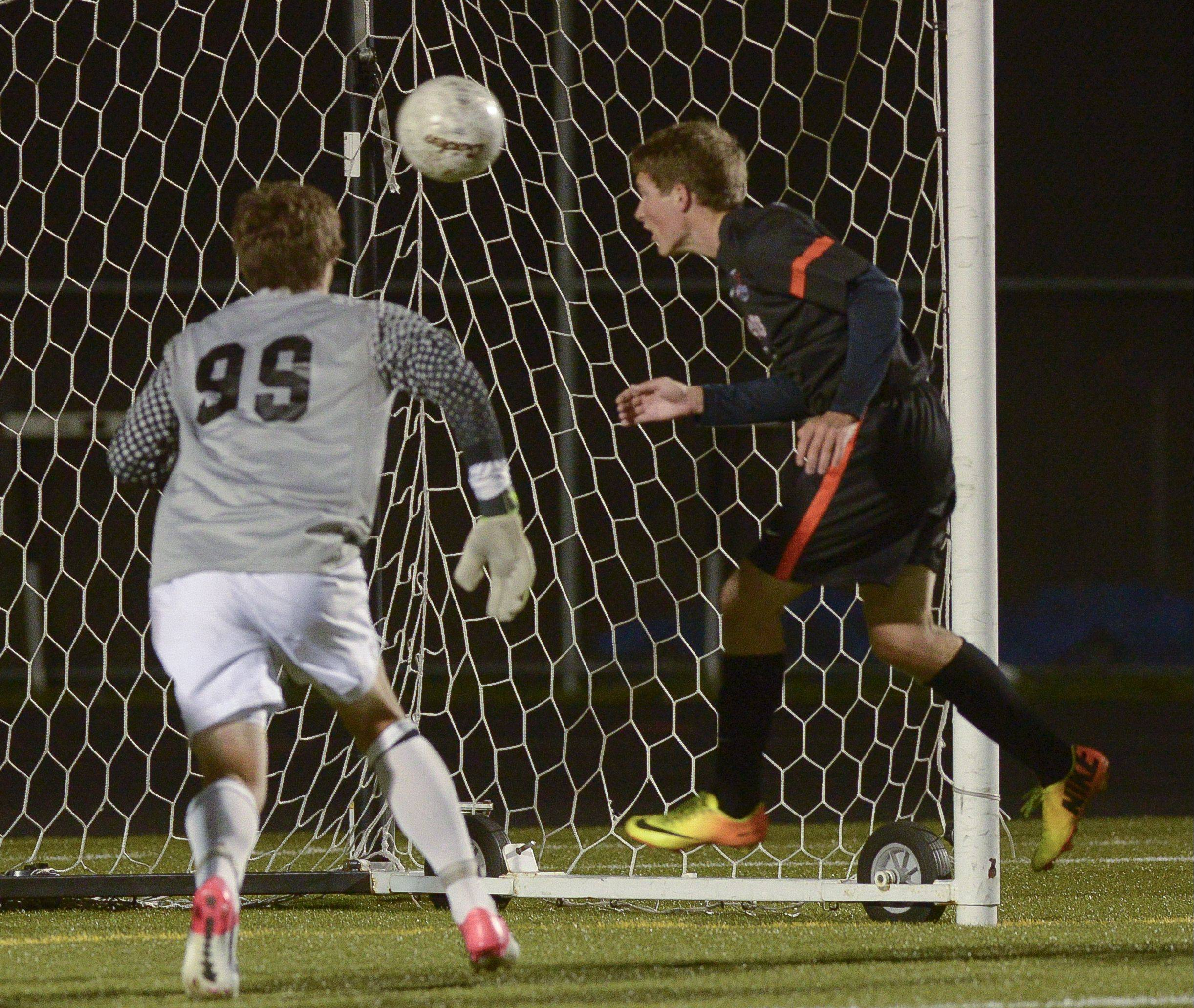 Above: Tyler Robbins of St. Charles East heads in the ball for a goal past Metea Valley's Tim Howard Wednesday in Aurora.Right: St. Charles East's Rob Wolak pressures Metea Valley's Jake Celinski.
