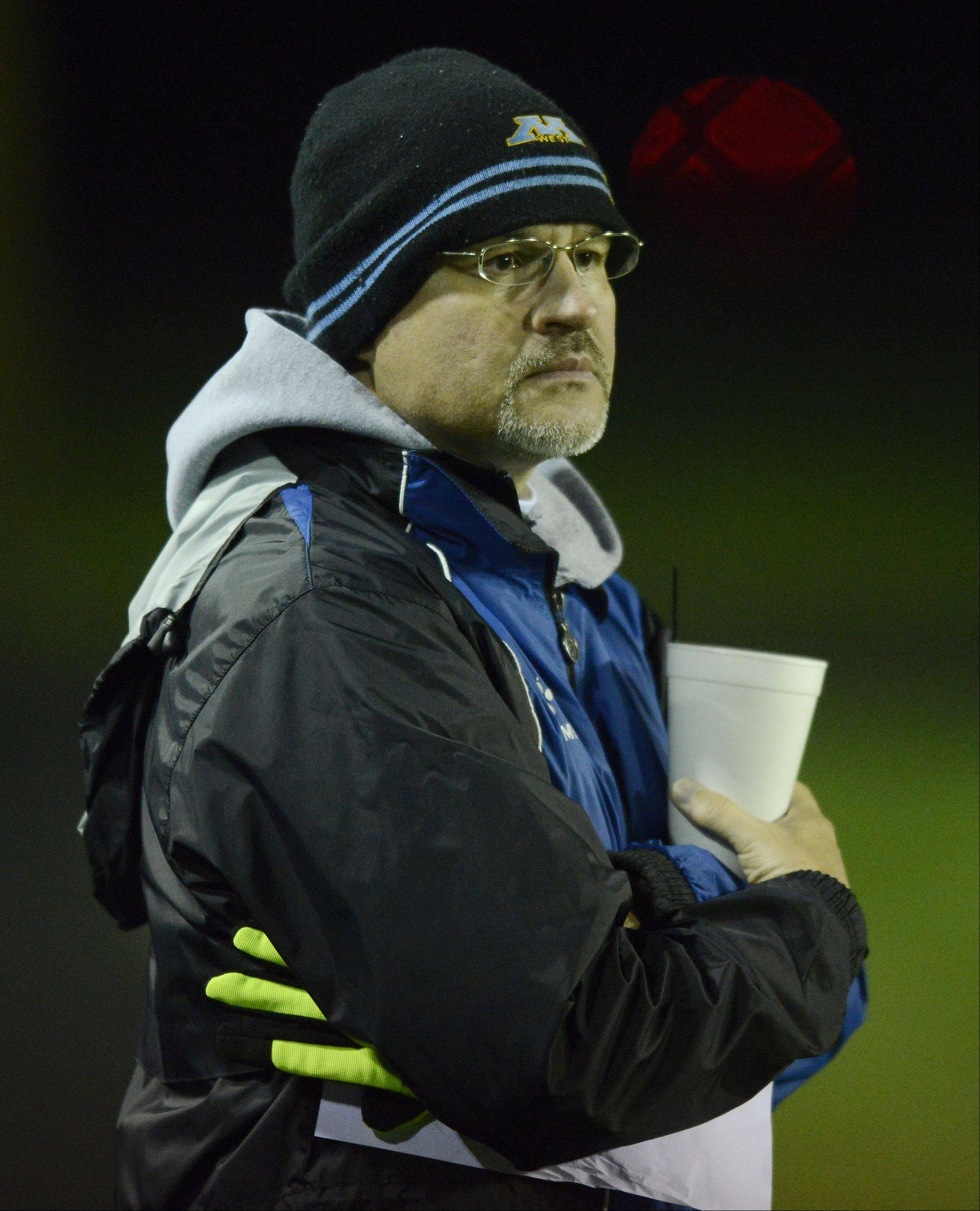 Maine West boys soccer coach Alan Matan watches the action on the field during Wednesday's soccer game in Des Plaines.