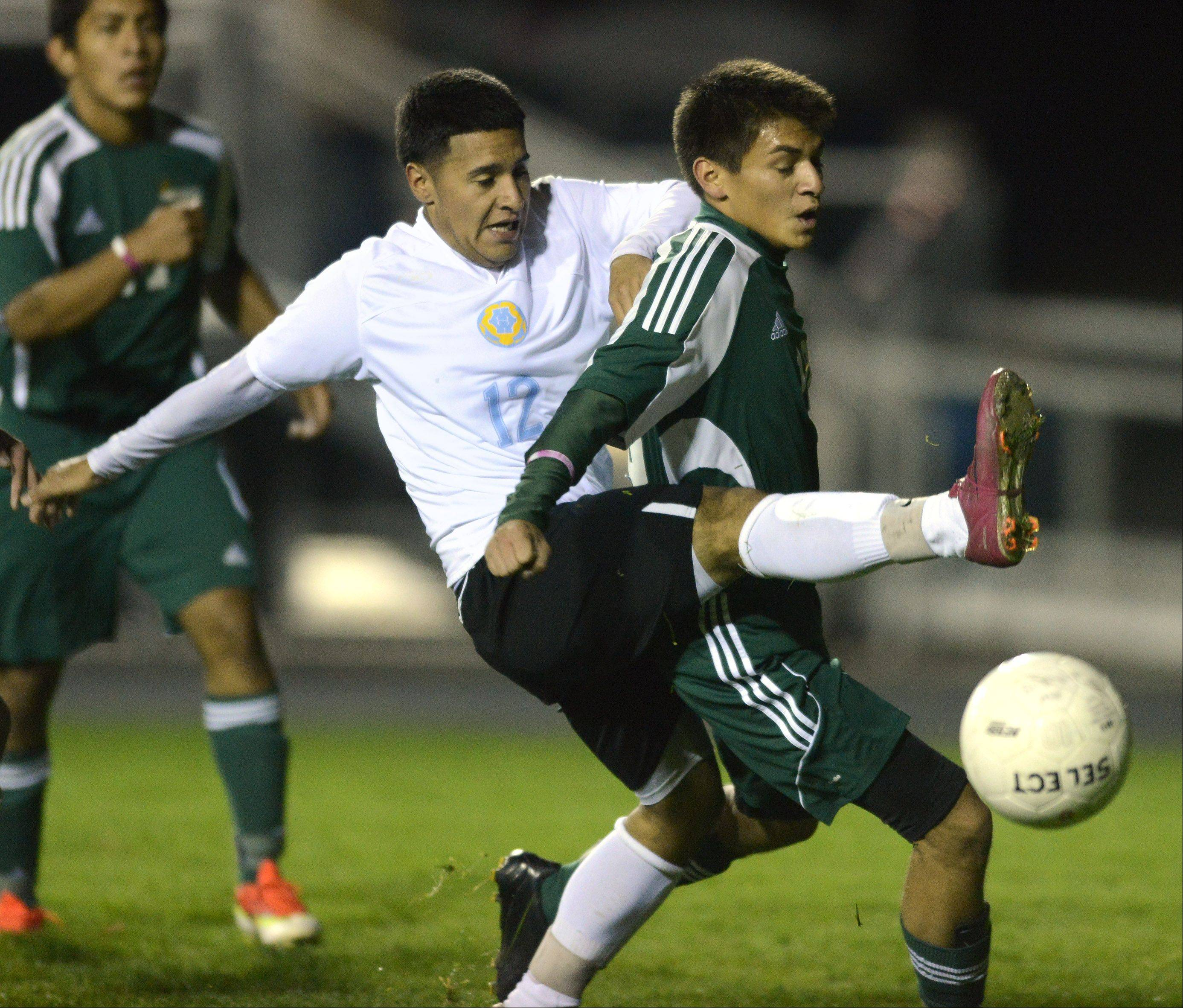 Maine West's Noe Moreno, left, gets tangled up with St. Patrick's Eric Rodriguez during Wednesday's game in Des Plaines.