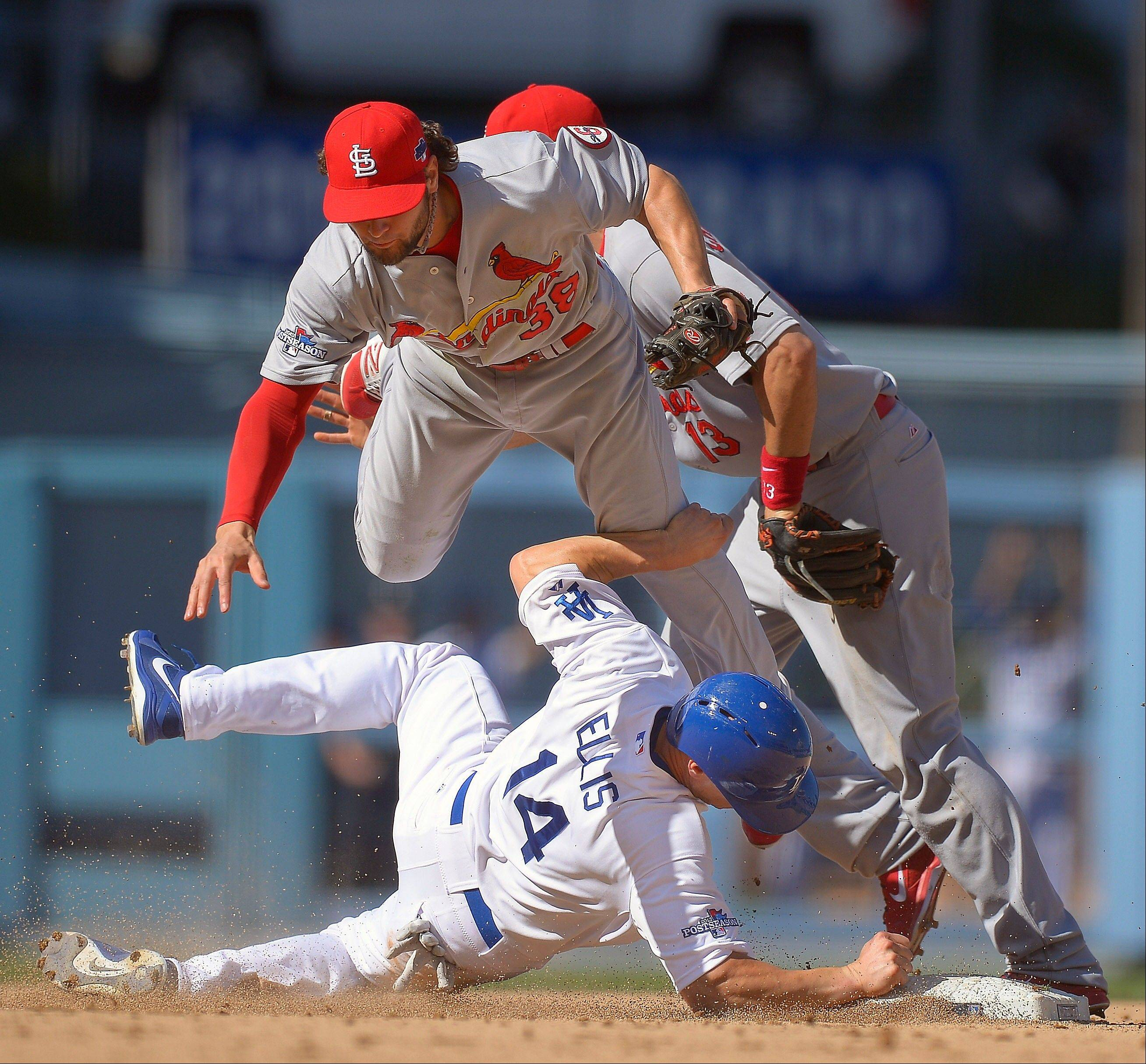 The Dodgers' Mark Ellis tries to break up a double play and gets tangled with the Cardinals' Pete Kozma (38) and Matt Carpenter (13) during the third inning.