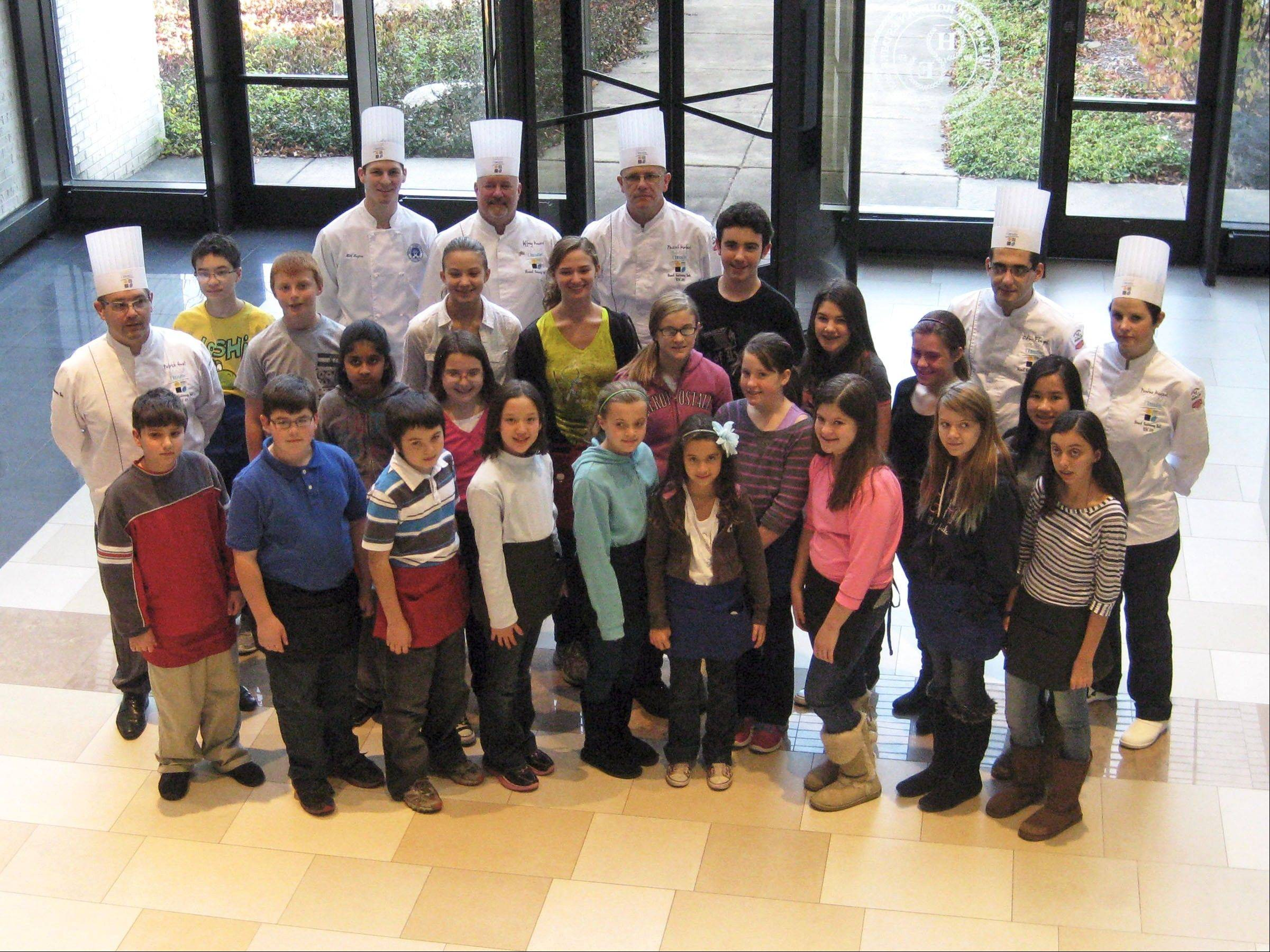 Chef Patrick Guat, left, and his culinary students pose with last year's children's cooking class at the Village Hall.