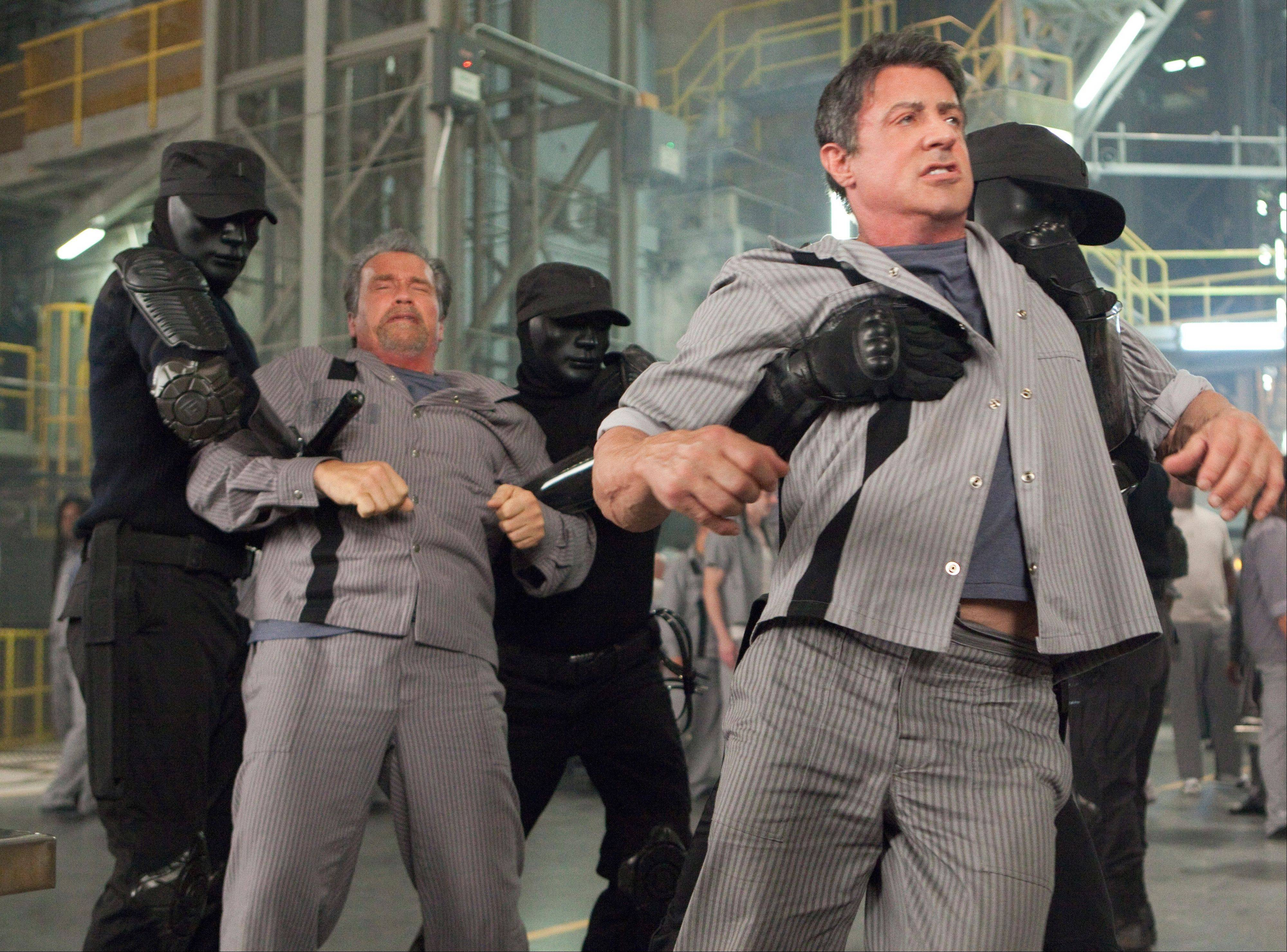 "Prison guards looking suspiciously like the Gray Man Group grab inmates Rottmayer (Arnold Schwarzenegger), left, and Breslin (Sylvester Stallone) in the dopey action film ""Escape Plan."""