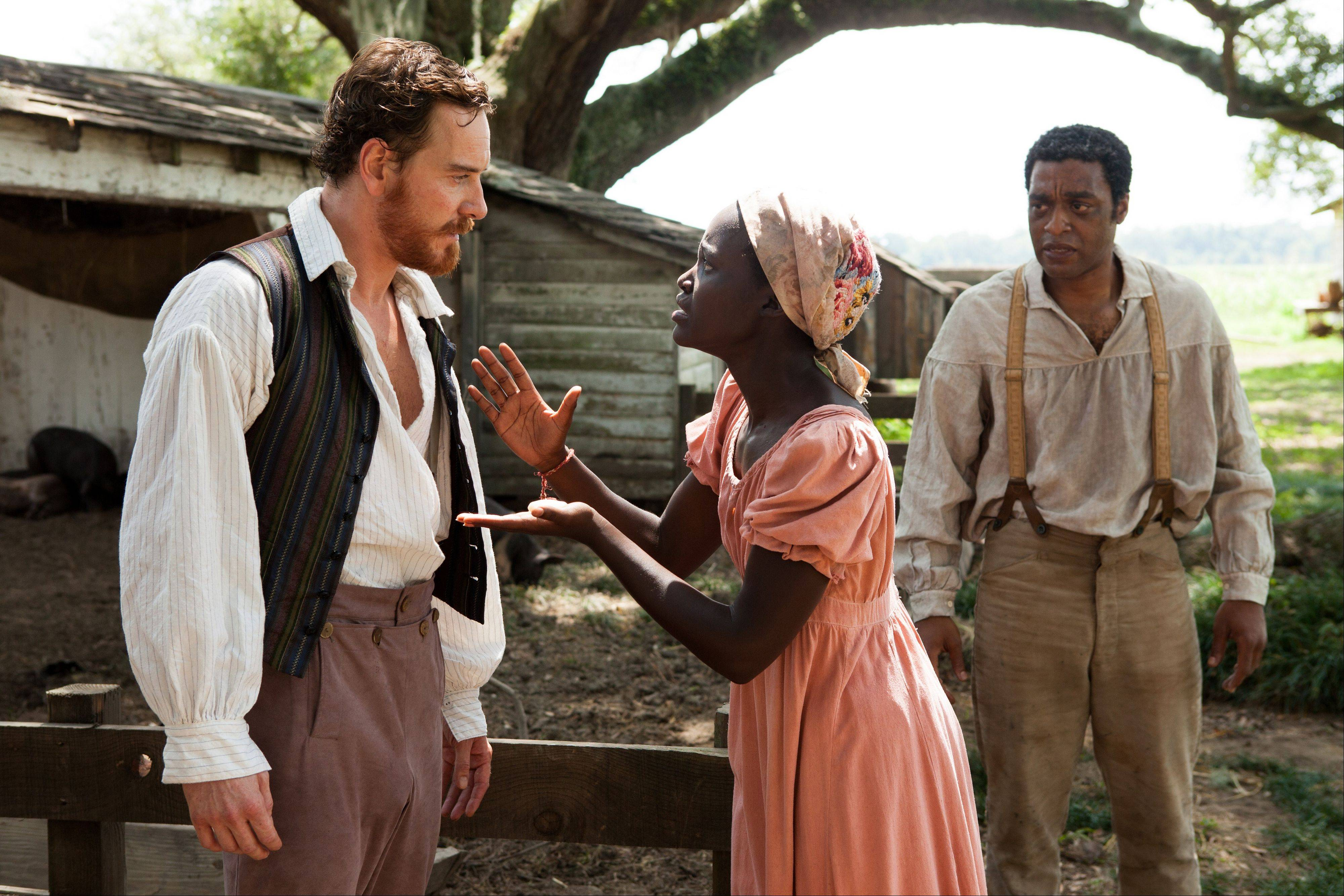 "Patsey (Lupita Nyong'o) pleads with plantation owner Epps (Michael Fassbender) as Northup (Chiwetel Ejiofor) stands down in Steve McQueen's ""12 Years a Slave."""