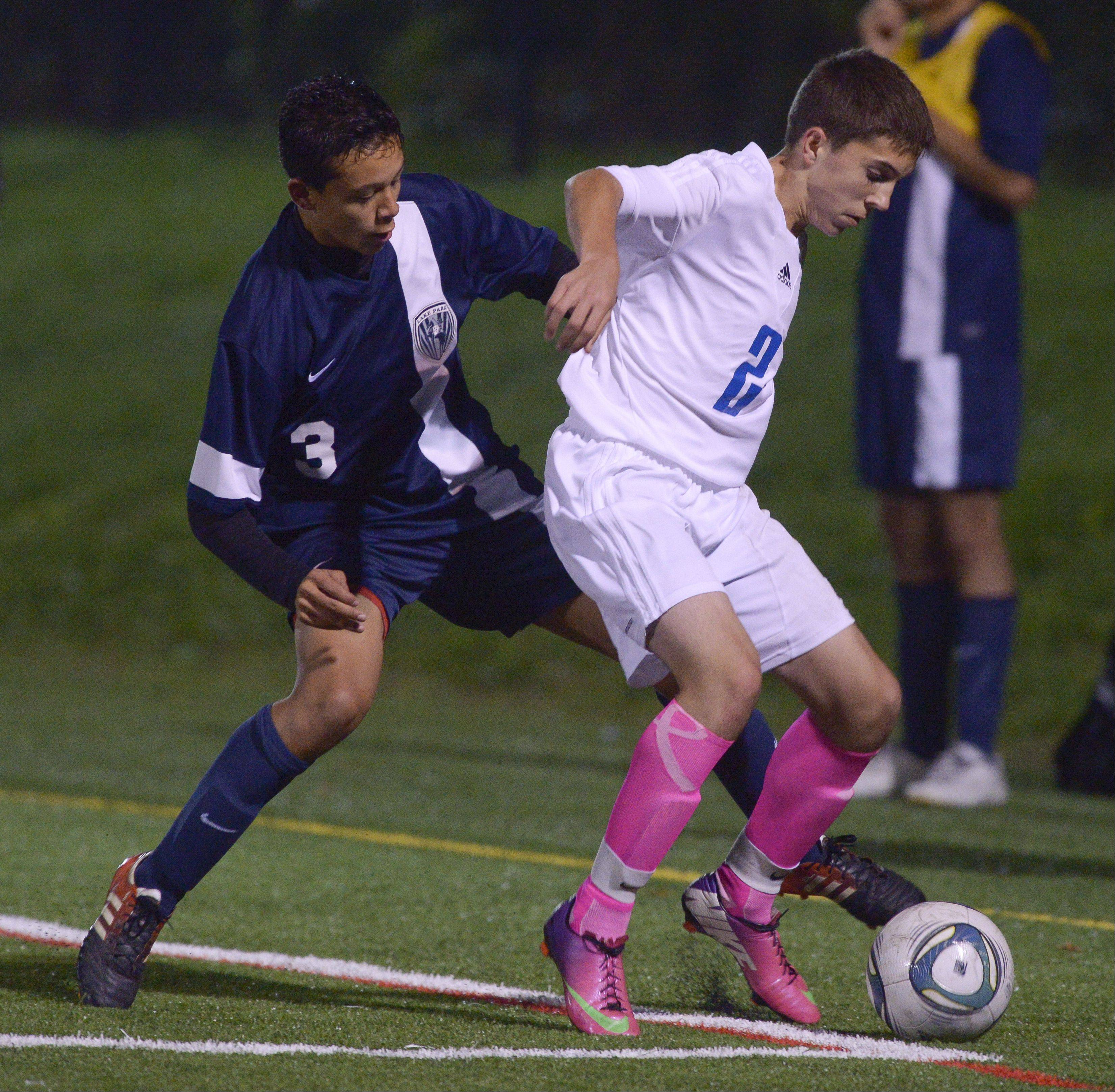 Kris Lopez of Lake Park and Bernard Plawinski of Fenton battle for control of the ball during varsity boys soccer in Bensonville, Thursday.