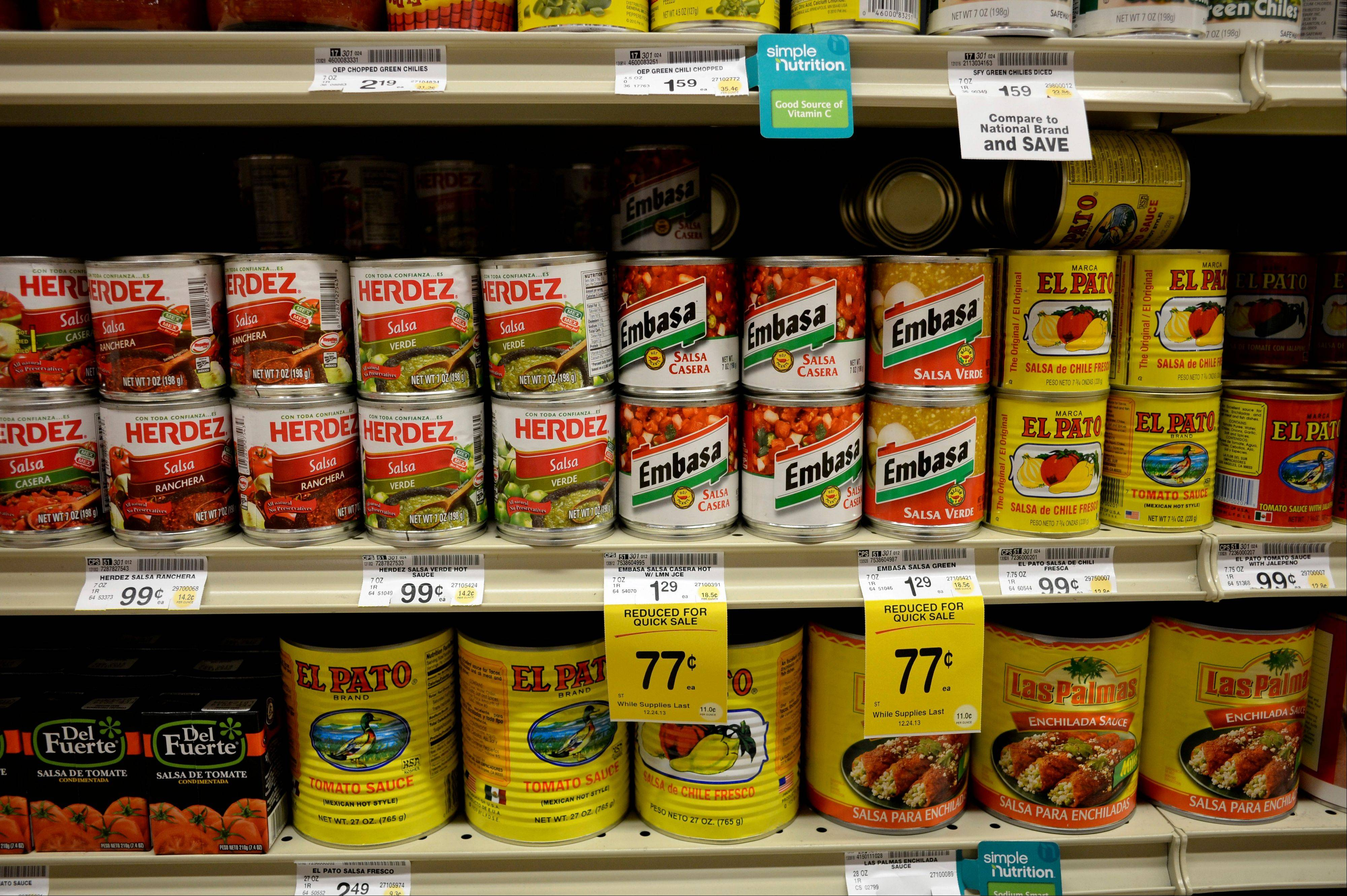"Salsas and other items are seen in the International food aisle of a grocery store in Washington. These days, tortillas outsell burger and hot dog buns; sales of tortilla chips trump potato chips; and tacos and burritos have become so ubiquitously ""American,"" most people don�t even consider them ethnic."