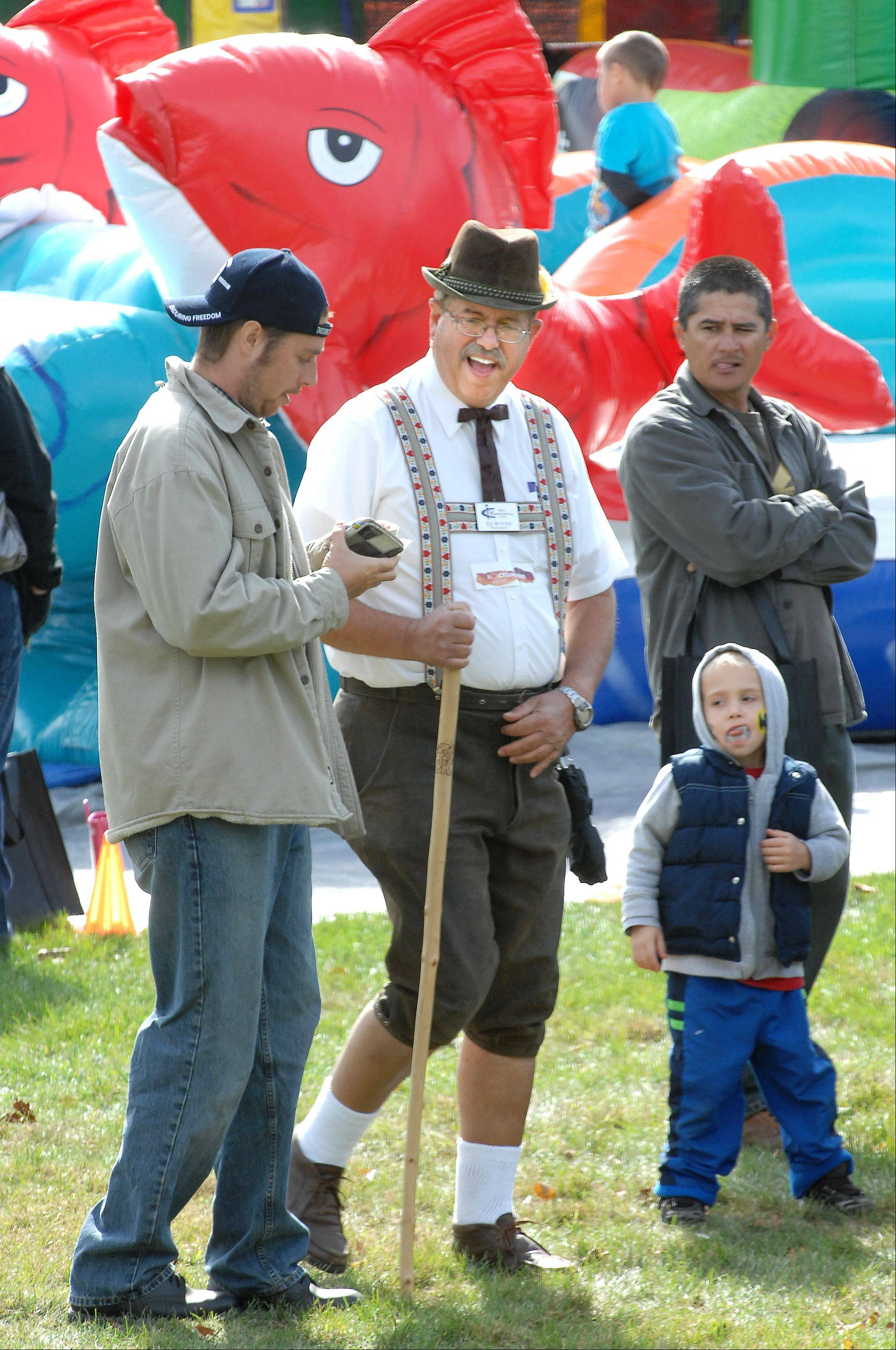 Carpentersville Village President Ed Ritter walks in the crowd wearing traditional Bavarian lederhosen during the 2011 Oktoberfest in Carpenter Park.
