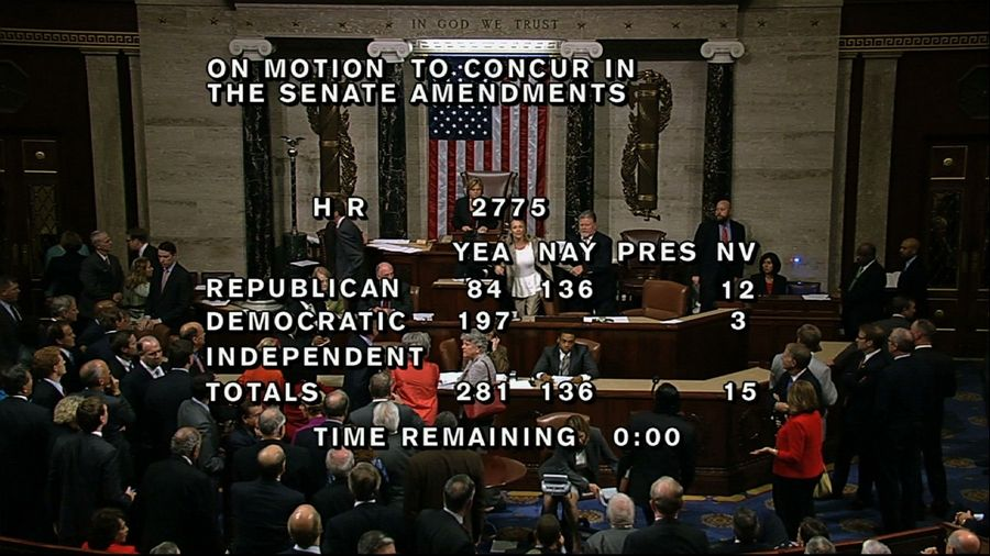 "In this image from House Television, with partial voting totals on the screen, a woman, at the rostrum just below the House presiding officer, seen between the ""yea"" and ""nay"" wording, is removed from the House chamber after she began shouting during the vote for the bill to end the partial 16-day government shutdown and to fund the government. The woman was described by lawmakers and aides as a longtime House stenographer."