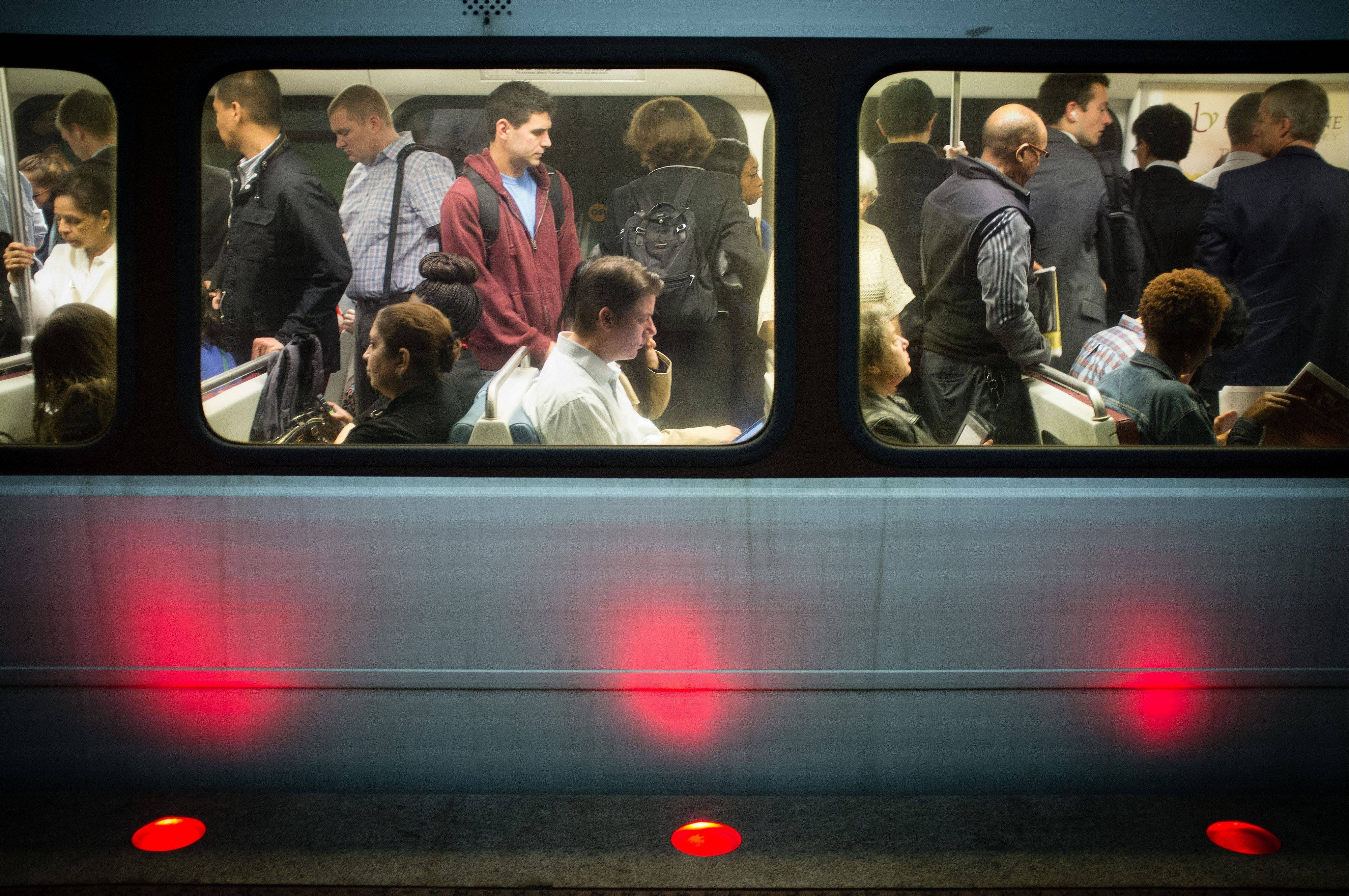 Passengers fill up Washington Metro subway cars in Arlington, Va., Thursday, as workers return to their jobs after Congress reached agreement a