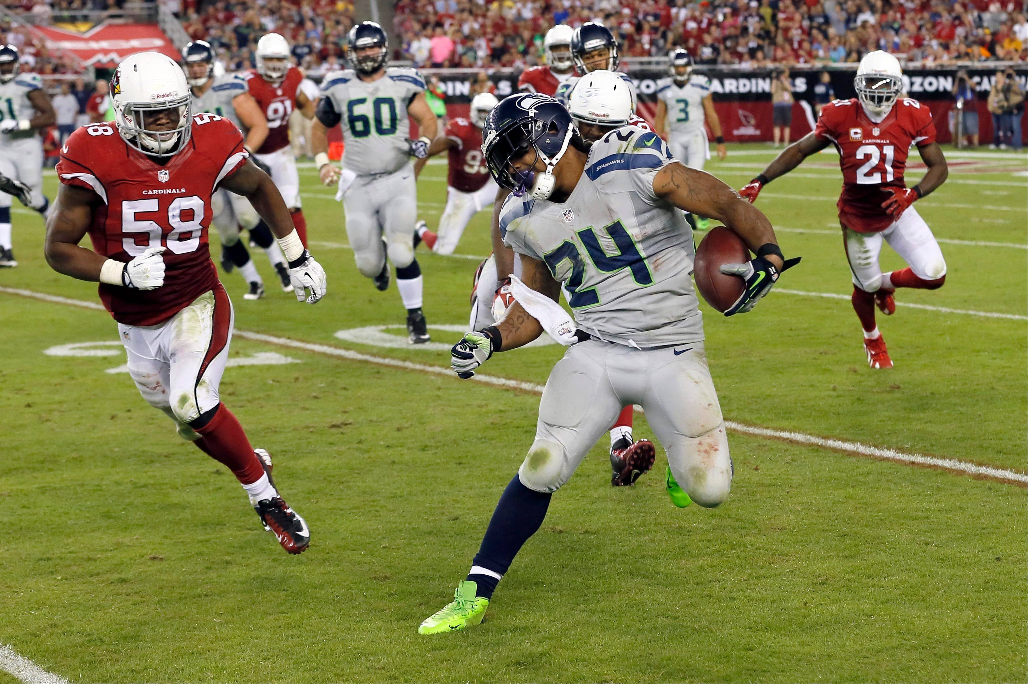 Seattle Seahawks running back Marshawn Lynch (24) tries to avoid Arizona Cardinals inside linebacker Daryl Washington (58) during the second half of an NFL football game, Thursday, Oct. 17, 2013, in Glendale, Ariz.