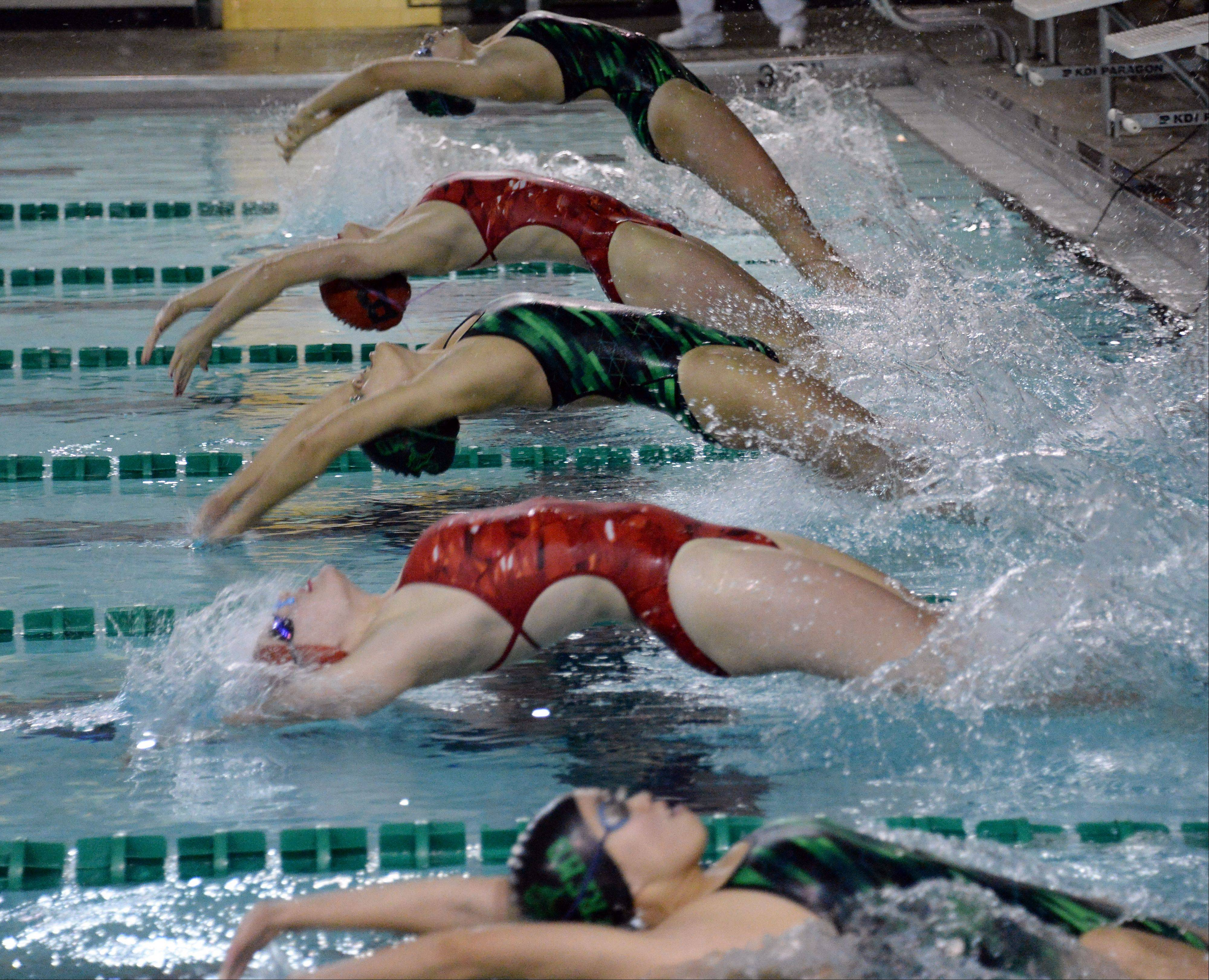 Fremd's Saki Takumiya, middle, and the rest of the varsity 100-meter backstroke heat leaves the blocks at Fremd on Thursday. Takumiya won the even in 1:07.49.