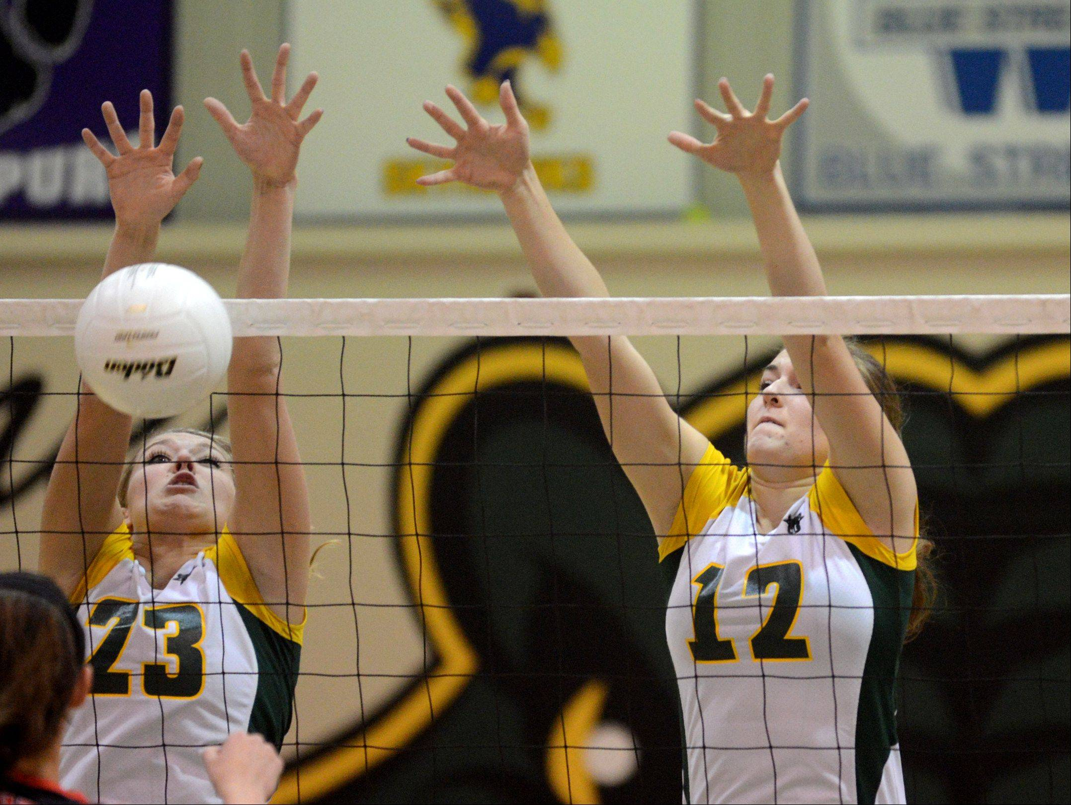 Crystal Lake South's Sara Mickow, left, and Nicole Slimko, right, block against Huntley during varsity volleyball at Crystal Lake on Thursday night.