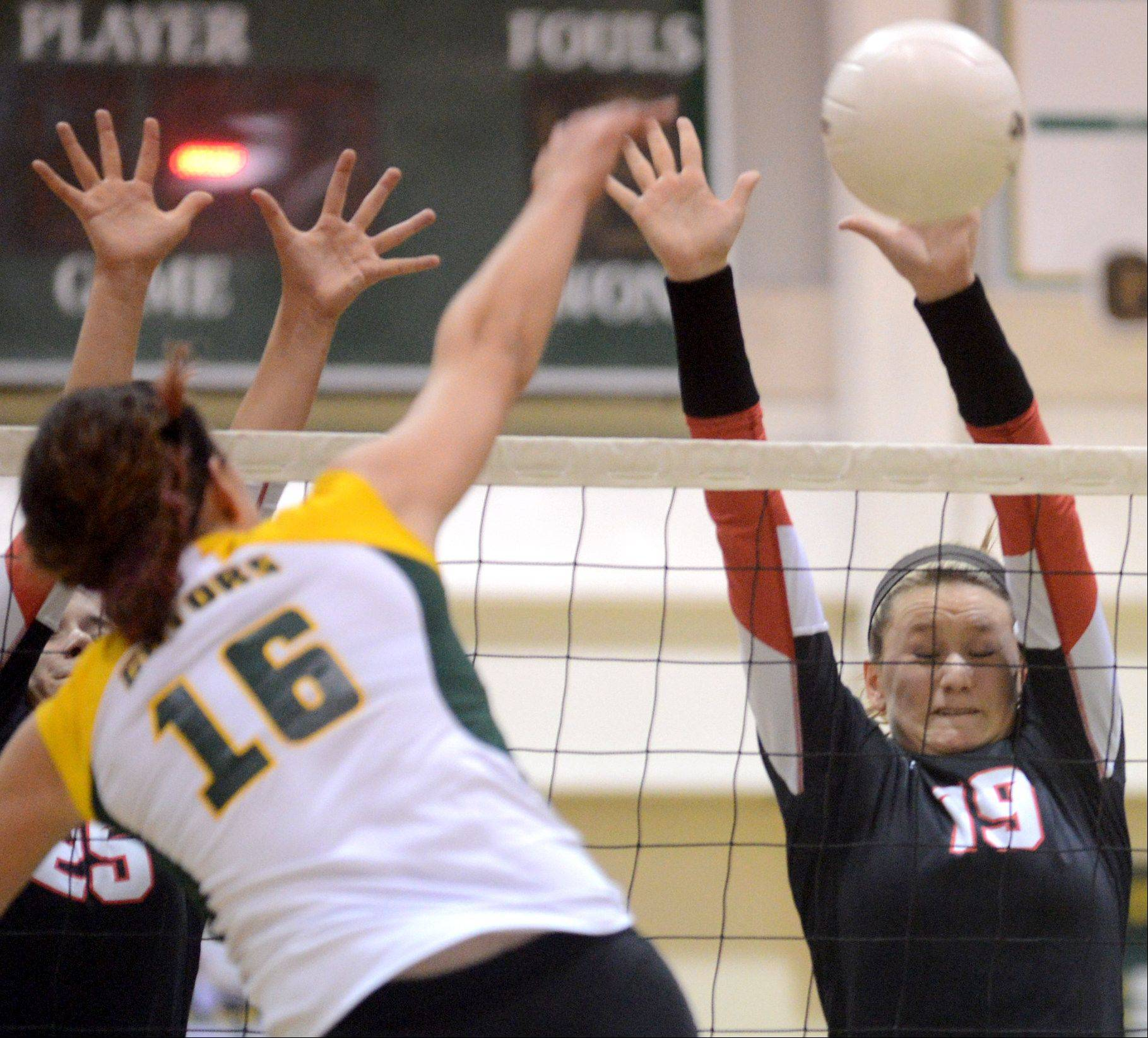 Crystal Lake South's Carly Nolan slams the ball against Huntley's Erin Erb, right, during varsity volleyball at Crystal Lake on Thursday night.