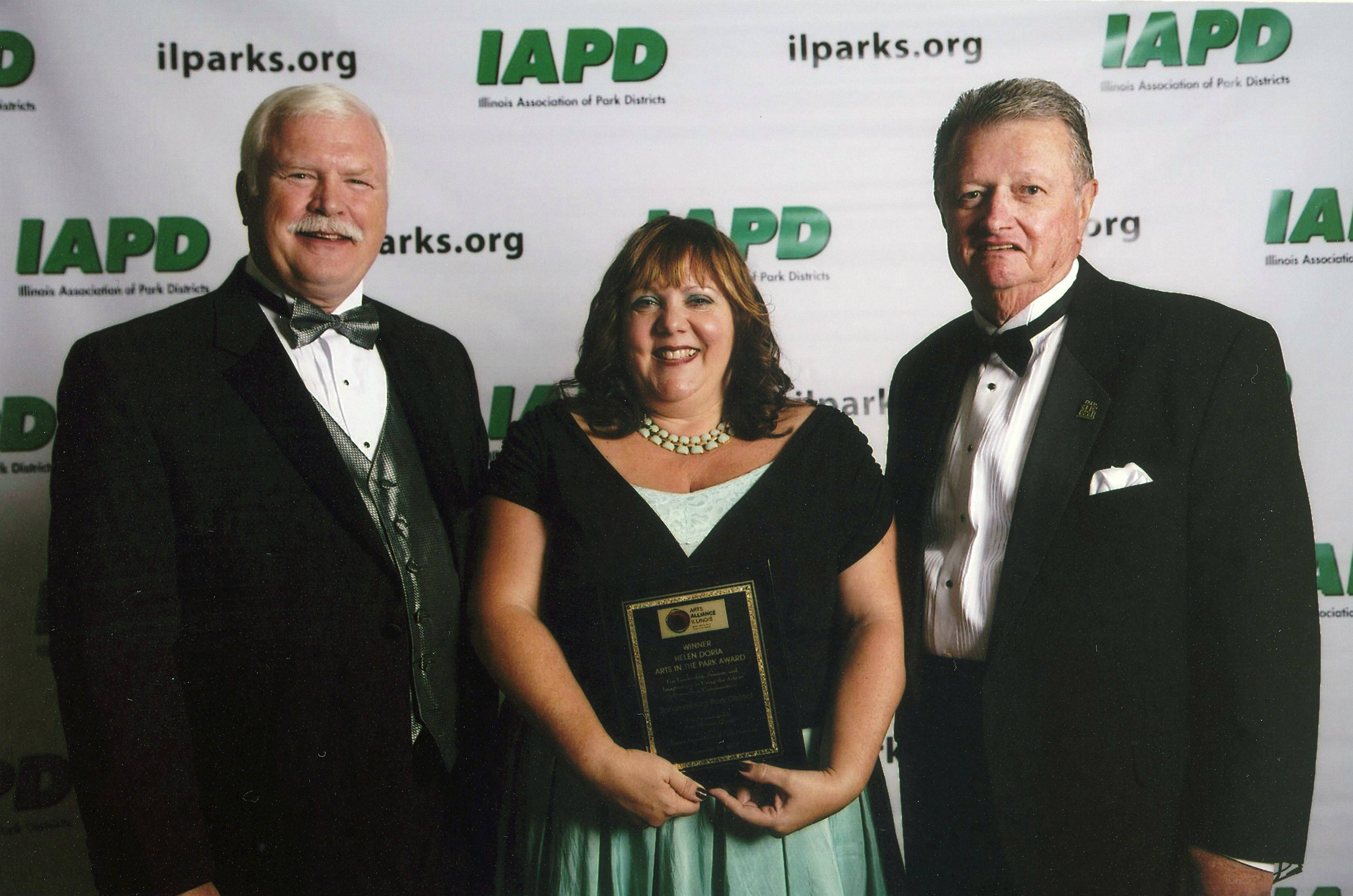 Illinois Association of Park Districts President and CEO Peter Murphy (left to right), Schaumburg Park District Cultural Arts Supervisor Beth Waller and IAPD Chairman Don Andersen stand with the Arts in the Park Award.