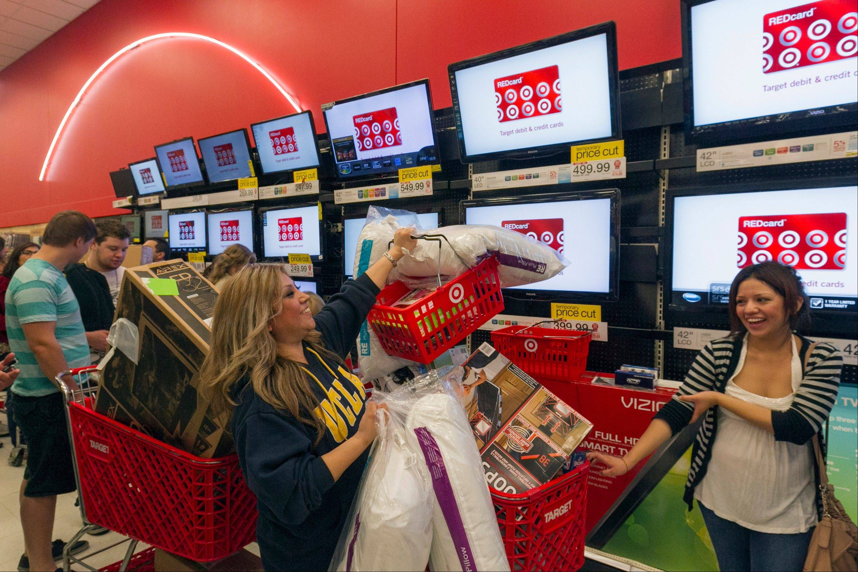 Associated Press/Nov. 22, 2012 Shopper Roxanna Garcia, middle, waits in line to pay for more than $1000 in gifts at the Target store in Burbank, Calif.