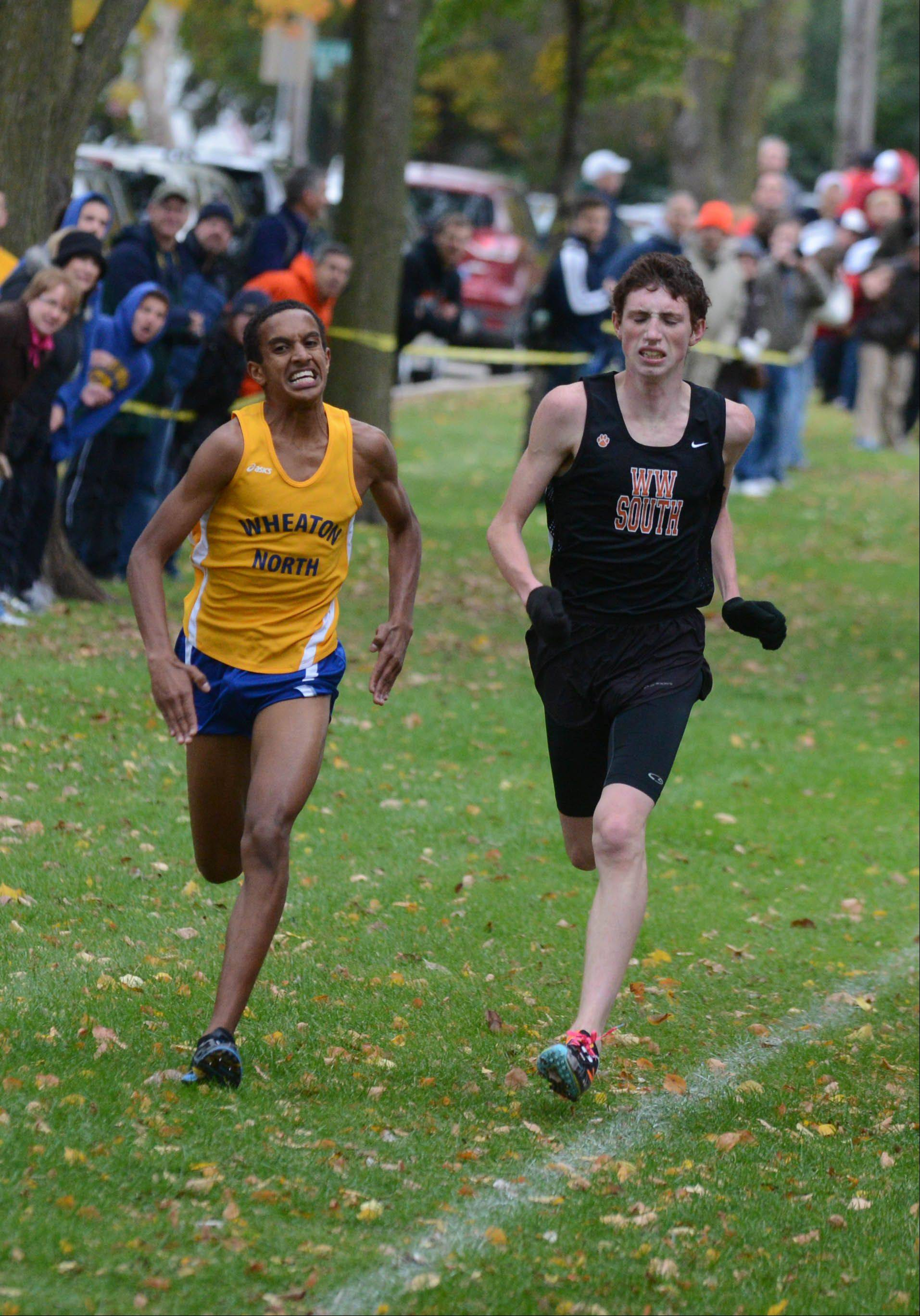 Joseph Emmanuel,left, of Wheaton North and Nolan McKenna of Wheaton Warrenville South race for the line during the DuPage Valley Conference boys and girls cross country meet Friday in Lombard.