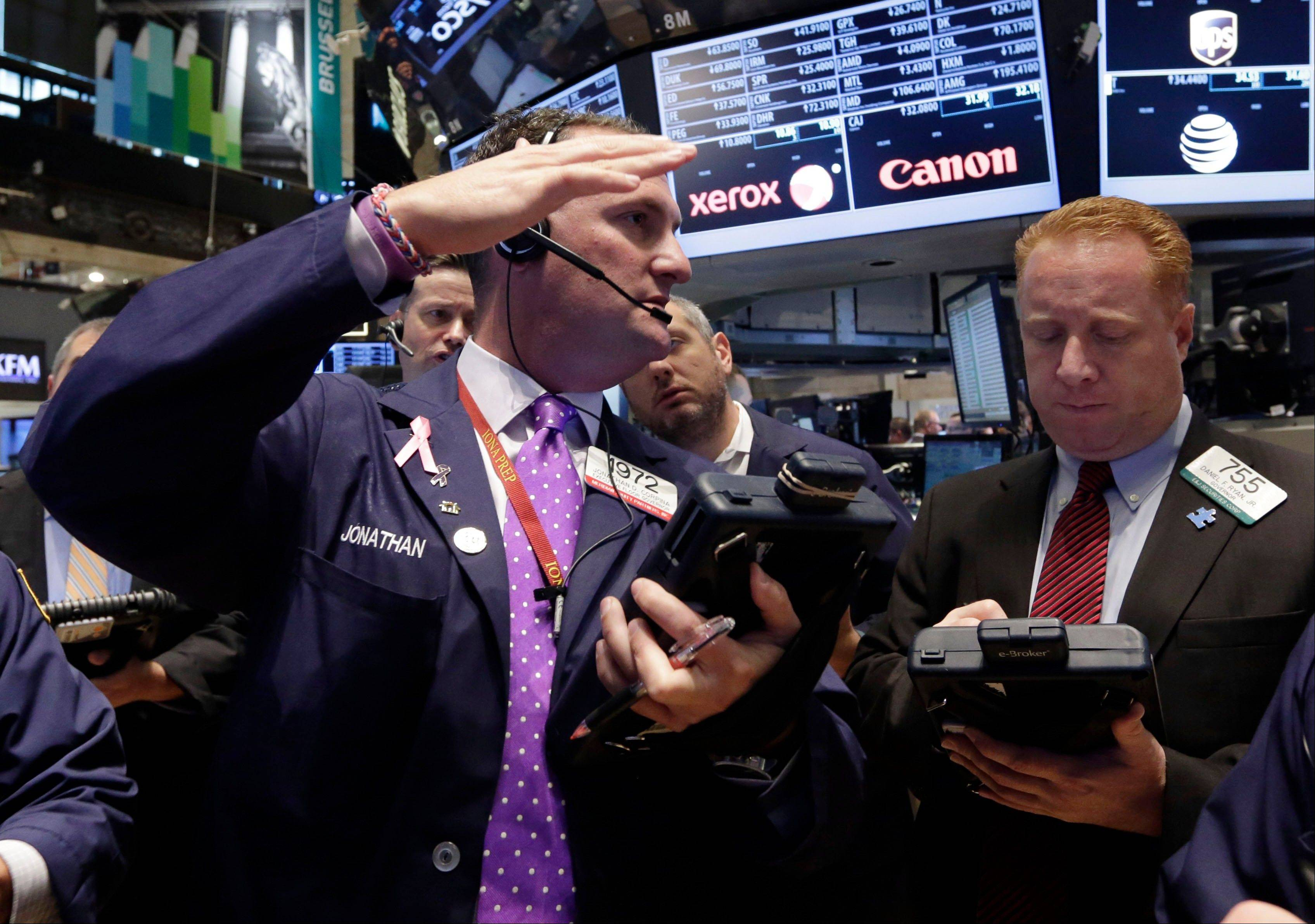 Jonathan Corpina, left, talks Friday with fellow trader Dan Ryan on the floor of the New York Stock Exchange.