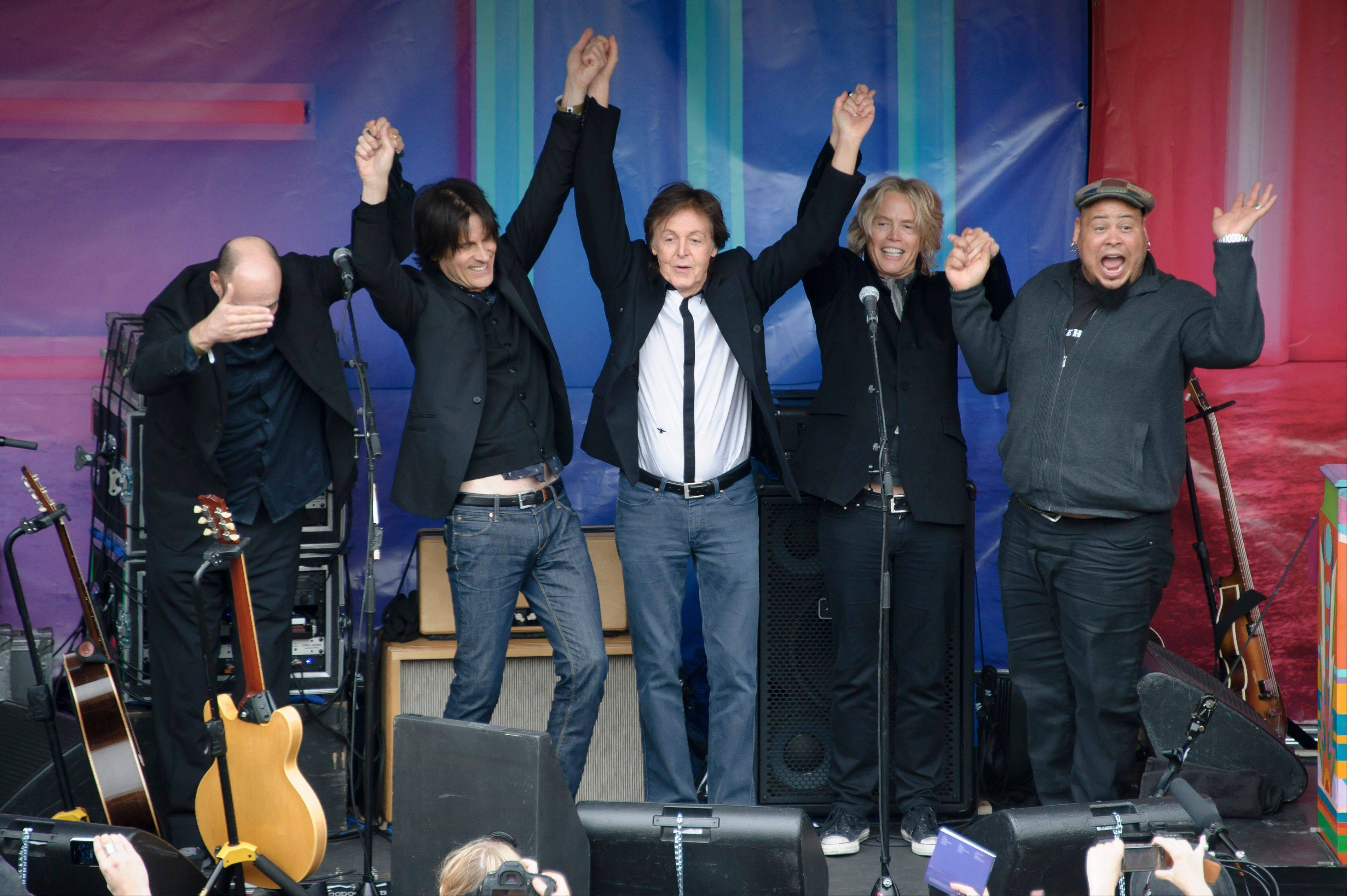 British singer Sir Paul McCartney and his band acknowledge the crowd after performing in Covent Garden, London, Friday. The surprise gig lasted for 20 minutes during lunchtime following a similar appearance in New York last Friday.