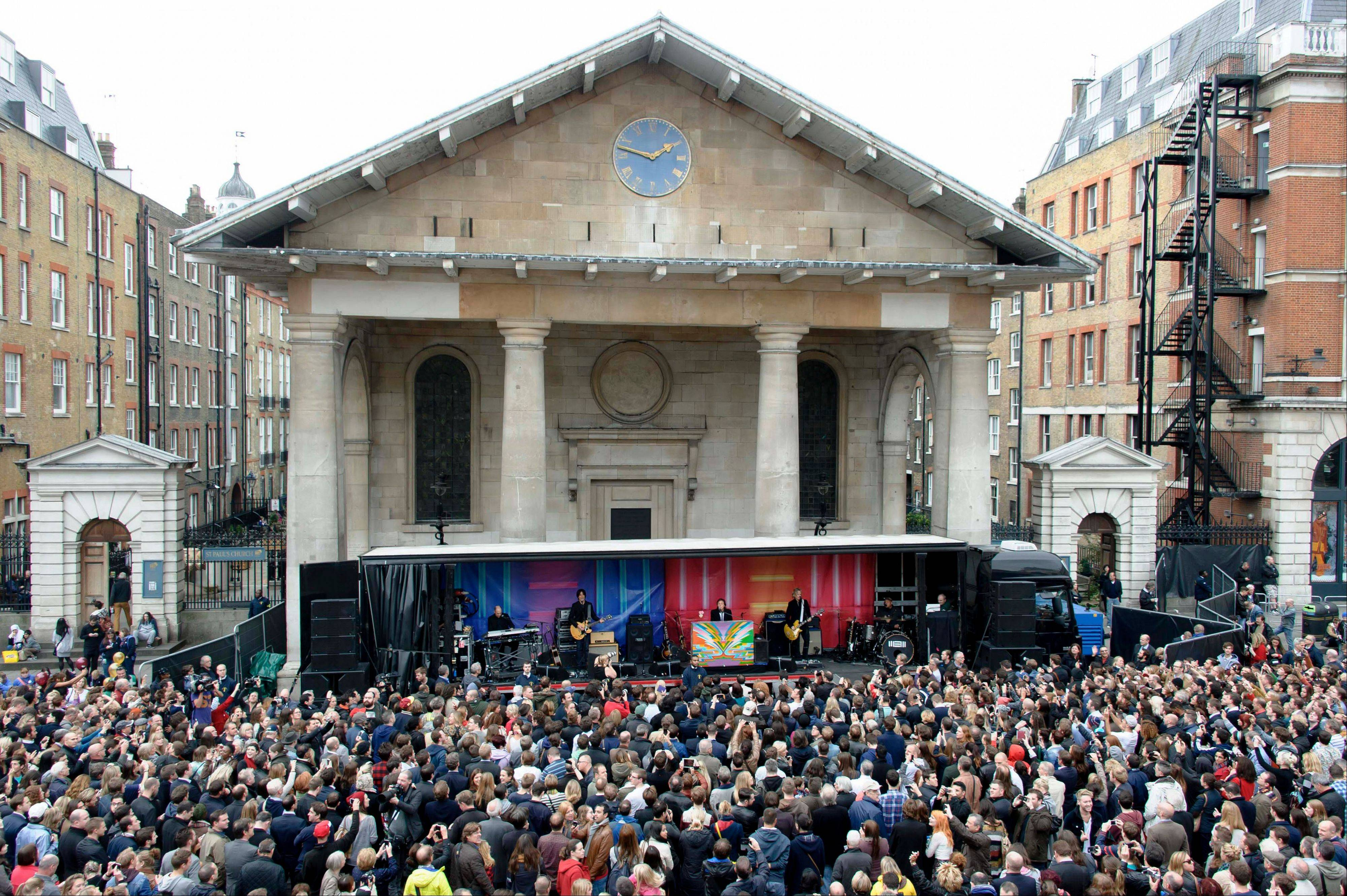 Crowds gather to watch Sir Paul McCartney and his band in Covent Garden, London, Friday. The surprise gig lasted for 20 minutes during lunchtime following a similar appearance in New York last Friday.