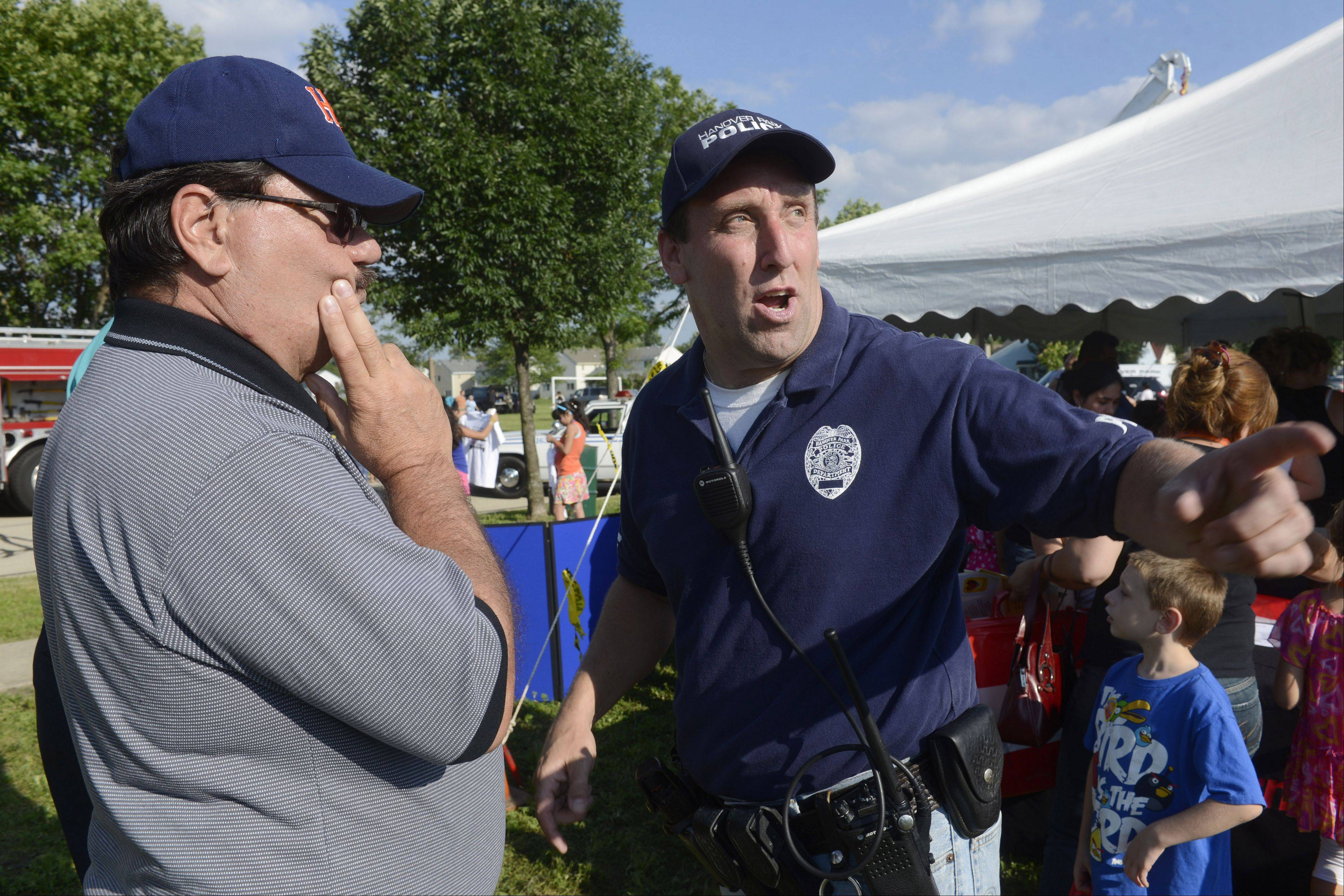 Hanover Park Police Officer George Sullivan, right, confers with Hanover Park Mayor Rodney Craig during the annual COPS Day Picnic at East Harbor Park in Hanover Park.