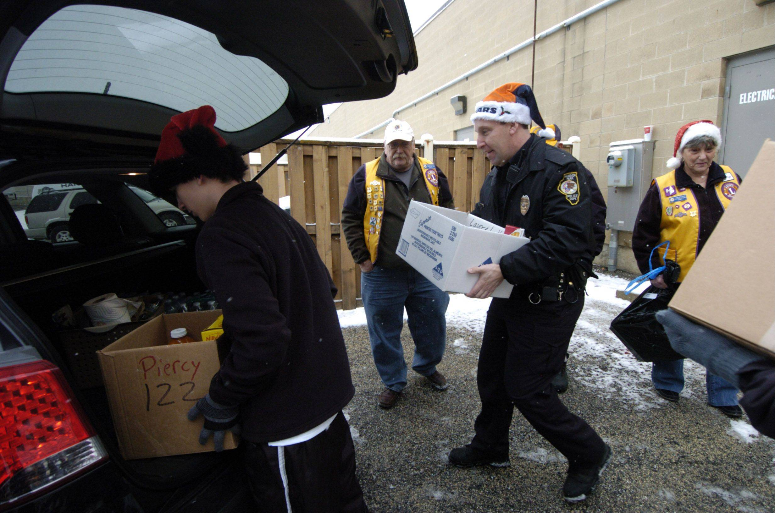 Officer Sullivan, center, helps load boxes of food and presents into a car during the Christmas season. The Hanover Park Lions Club, in cooperation with the Fraternal Order of Police, distributes food and Christmas presents to needy families.