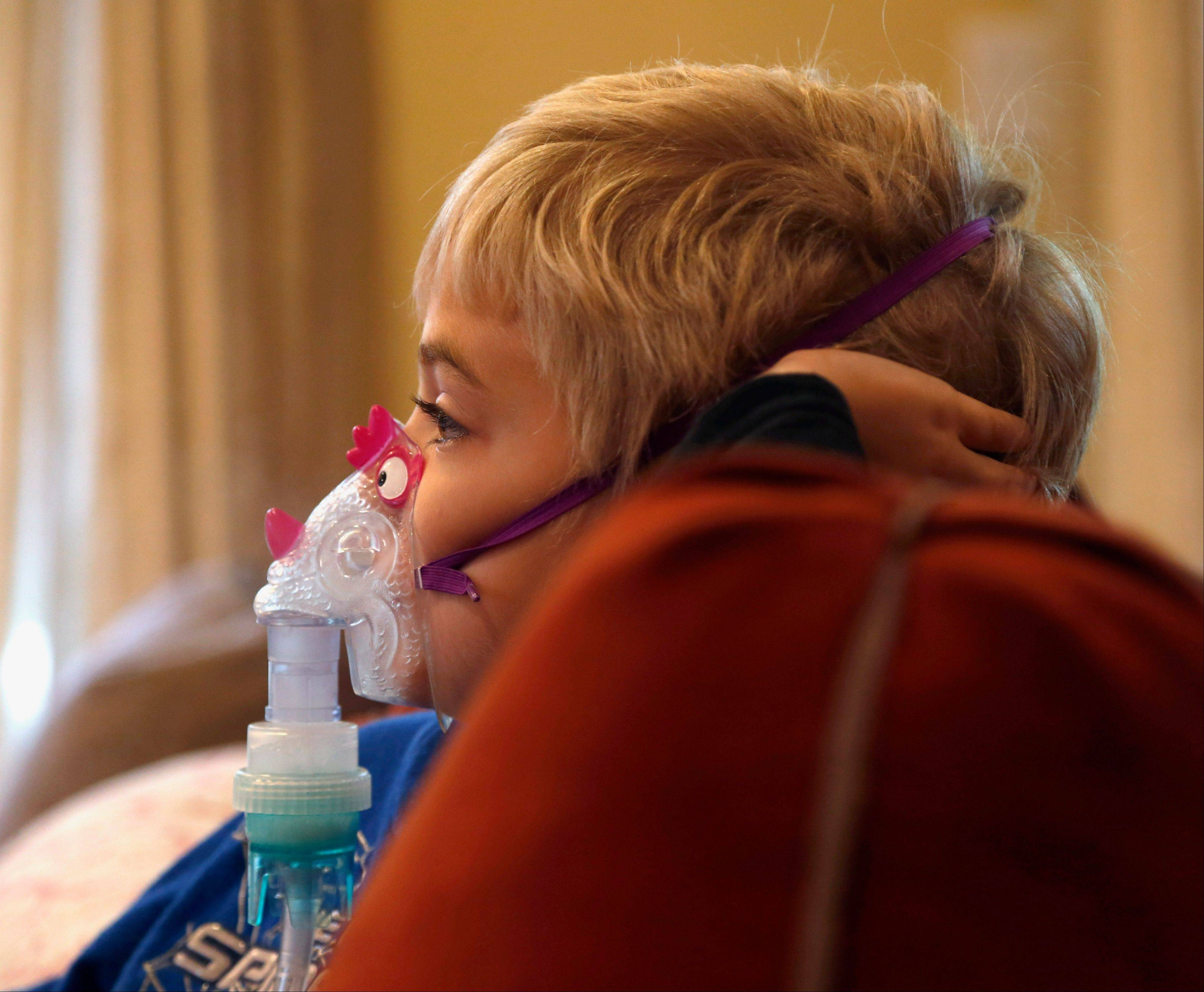 Carter Howard sits and watches a cartoon during his asthma treatment at his home in Northbrook. On the days when asthma gives Carter the most trouble, his mother is reminded how doctors at Rush University Medical Center had to stop submitting applications for research grants to study childhood asthma and other diseases and disorders due to the federal government shutdown.