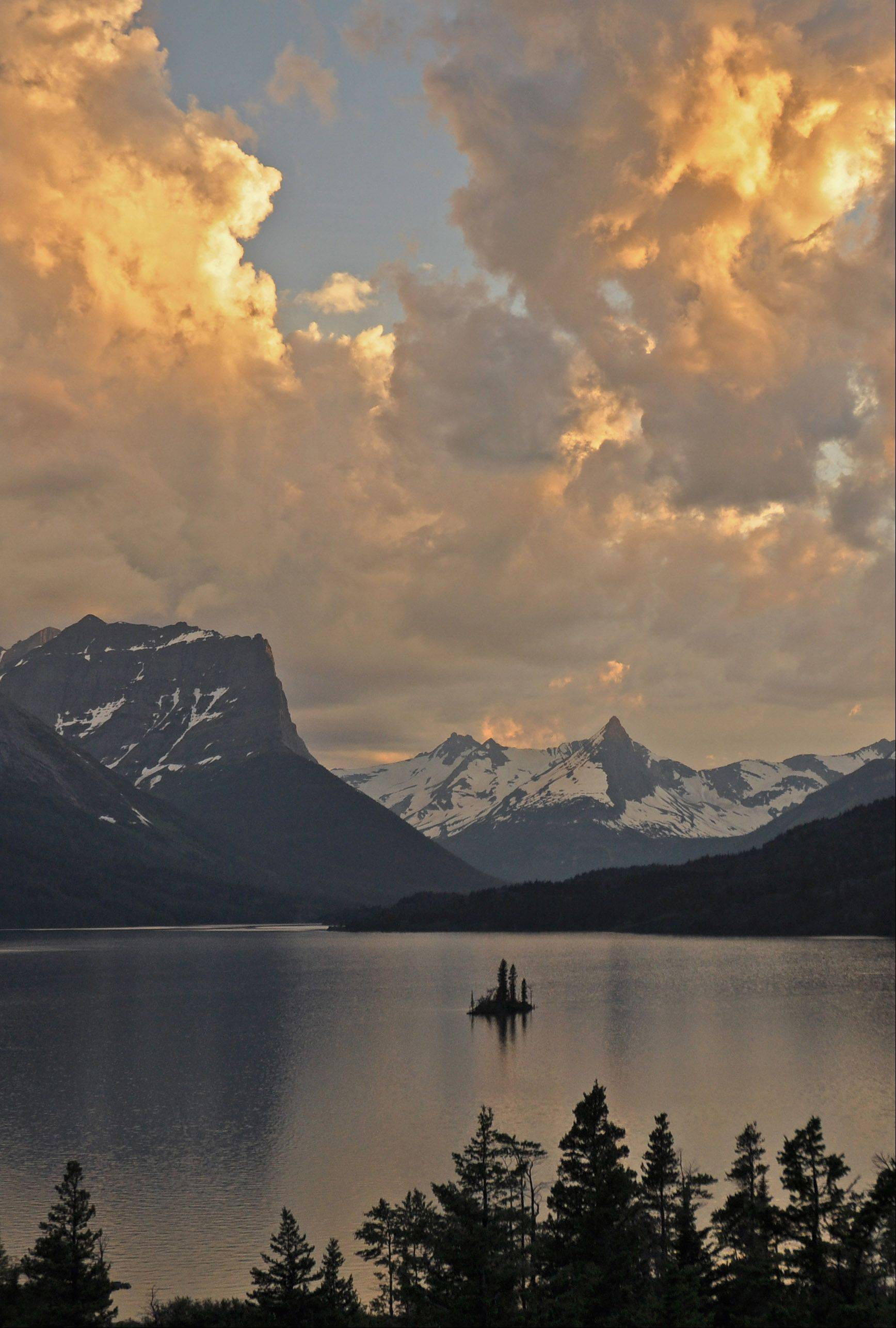 In Montana's Glacier National Park, dusk settles over St. Mary Lake and tiny Wild Goose Island. The last rays of sunset light up huge clouds forming over the park's glacier-carved mountains.