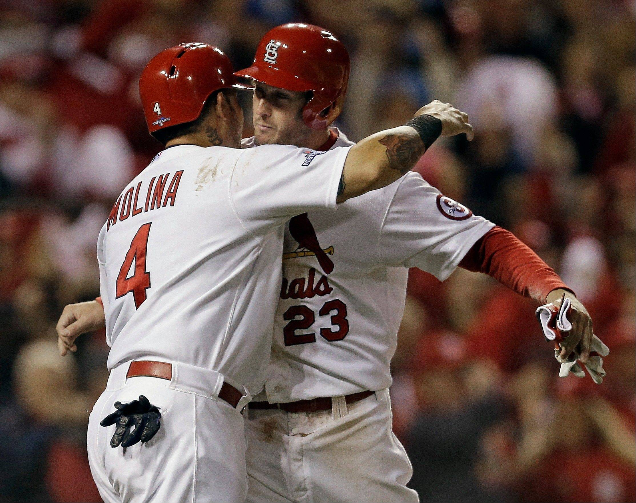 The Cardinals' David Freese and Yadier Molina celebrate after both scored on a hit by Shane Robinson during the third inning of Game 6 of the National League Championship Series against the Los Angeles Dodgers on Friday in St. Louis.