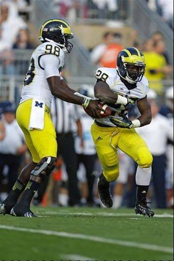 Michigan quarterback Devin Gardner fakes a handoff to running back Fitzgerald Toussaint during last week's game against Penn State in State College, Pa. Michigan desperately wants to improve its ground game without Gardner carrying the load.