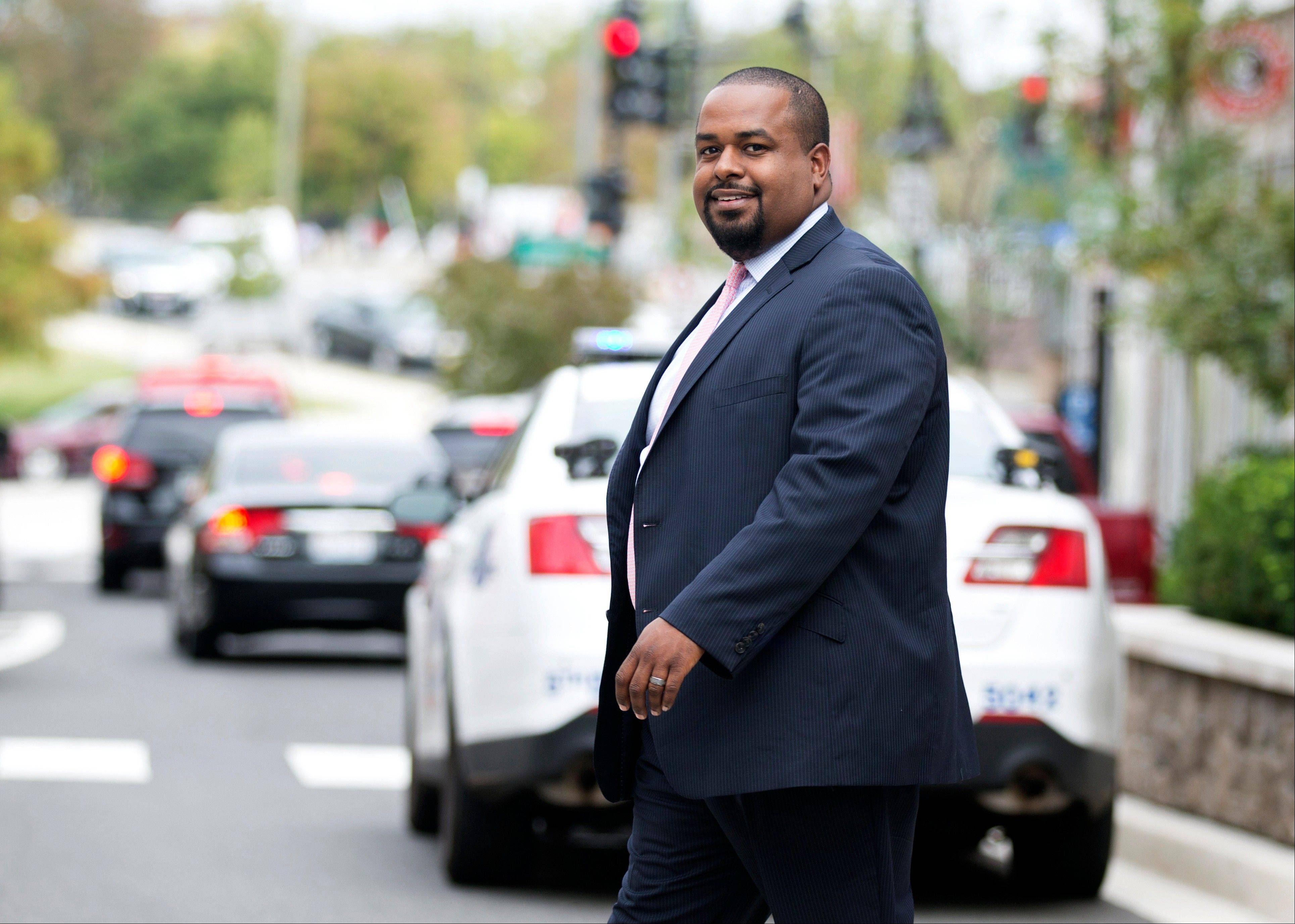 Joshua DuBois, an informal spiritual adviser to President Barack Obama, crosses a street Wednesday in Washington. �I�ve certainly seen the president�s faith grow in his time in office,� said DuBois.