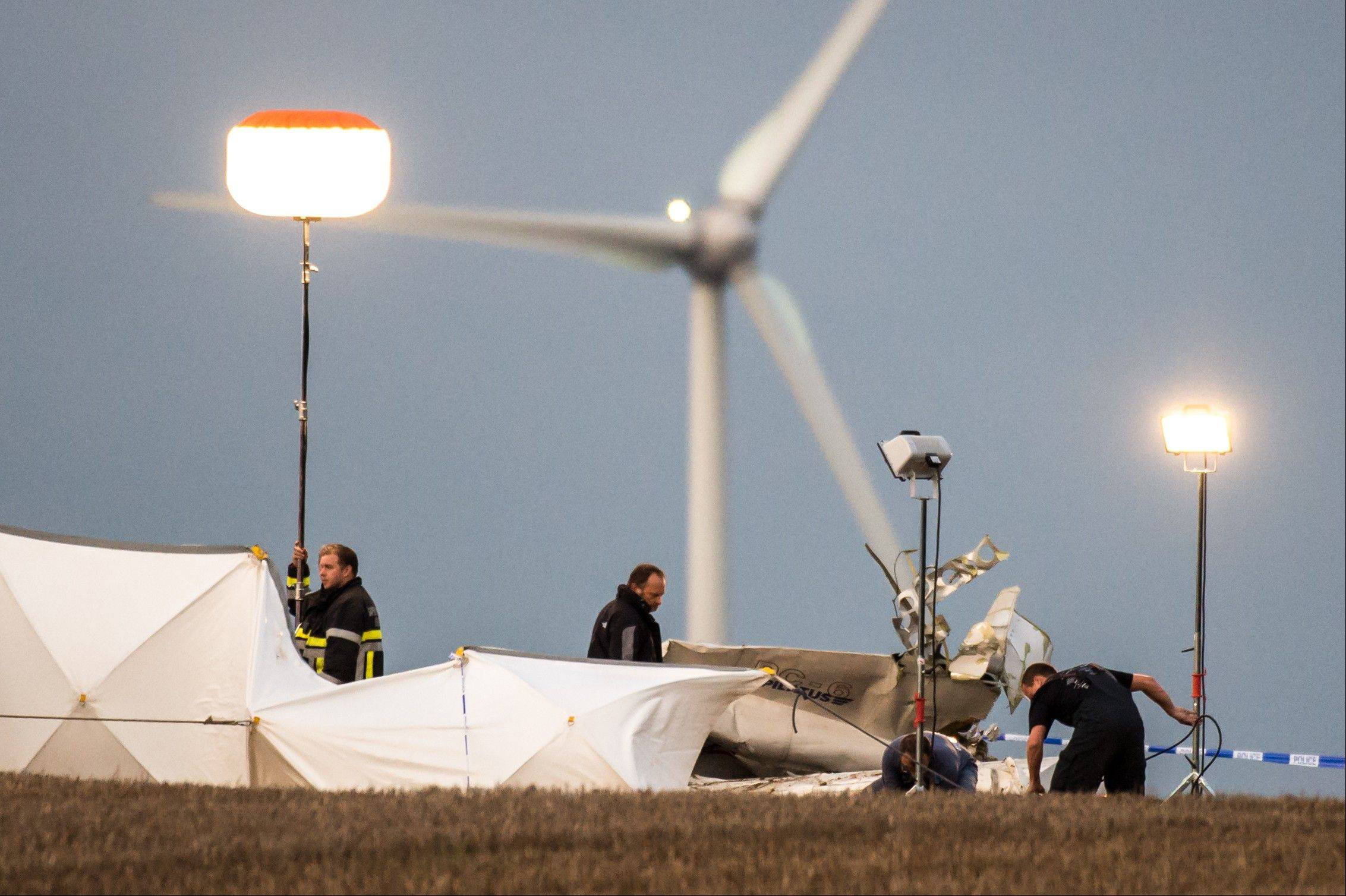 Rescue personnel work around the debris of a small plane which crashed in a field in Marchovelette, Belgium on Saturday.