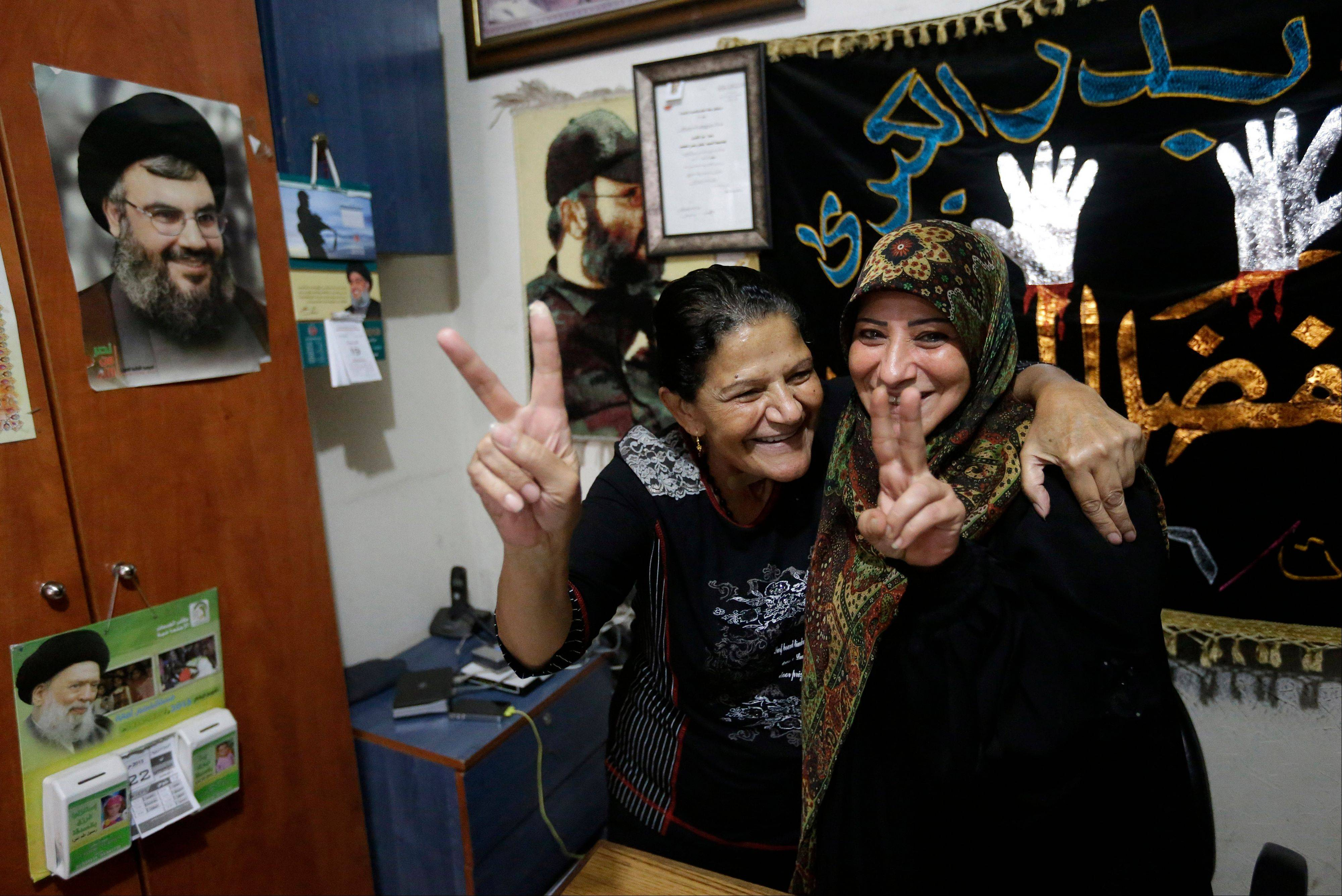 Relatives of nine Lebanese Shiite pilgrims who were kidnapped by a rebel faction in northern Syria in May 2012, flash victory signs Saturday as they celebrate news of their relatives release, in a suburb of Beirut, Lebanon.