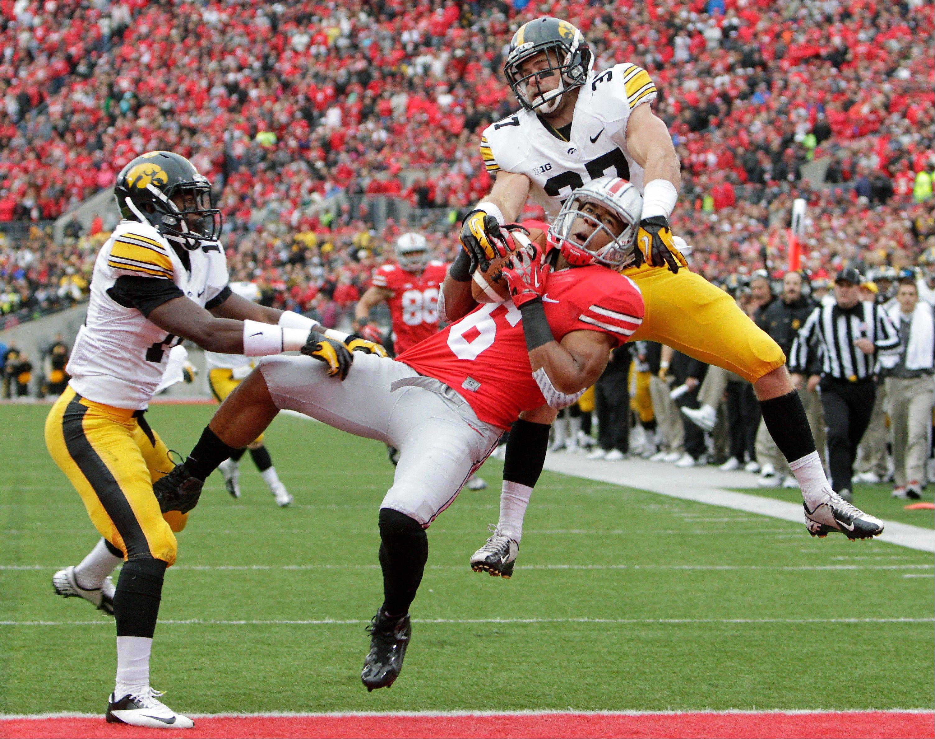Iowa defensive backs Desmond King, left, and John Lowdermilk, right, break up a pass intended for Ohio State wide receiver Evan Spencer, center, during the second quarter in Columbus, Ohio.