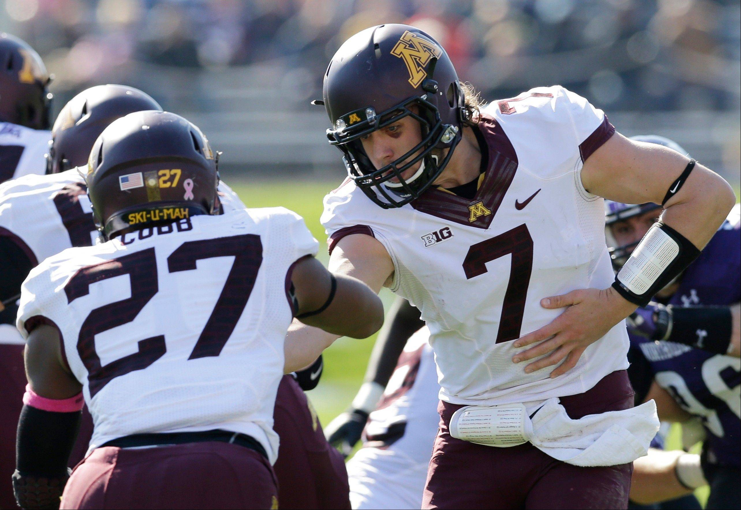 Minnesota quarterback Mitch Leidner (7) hands off the ball to running back David Cobb (27) during the first half of an NCAA college football game against Northwestern in Evanston, Ill., Saturday, Oct. 19, 2013. (AP Photo/Nam Y. Huh)