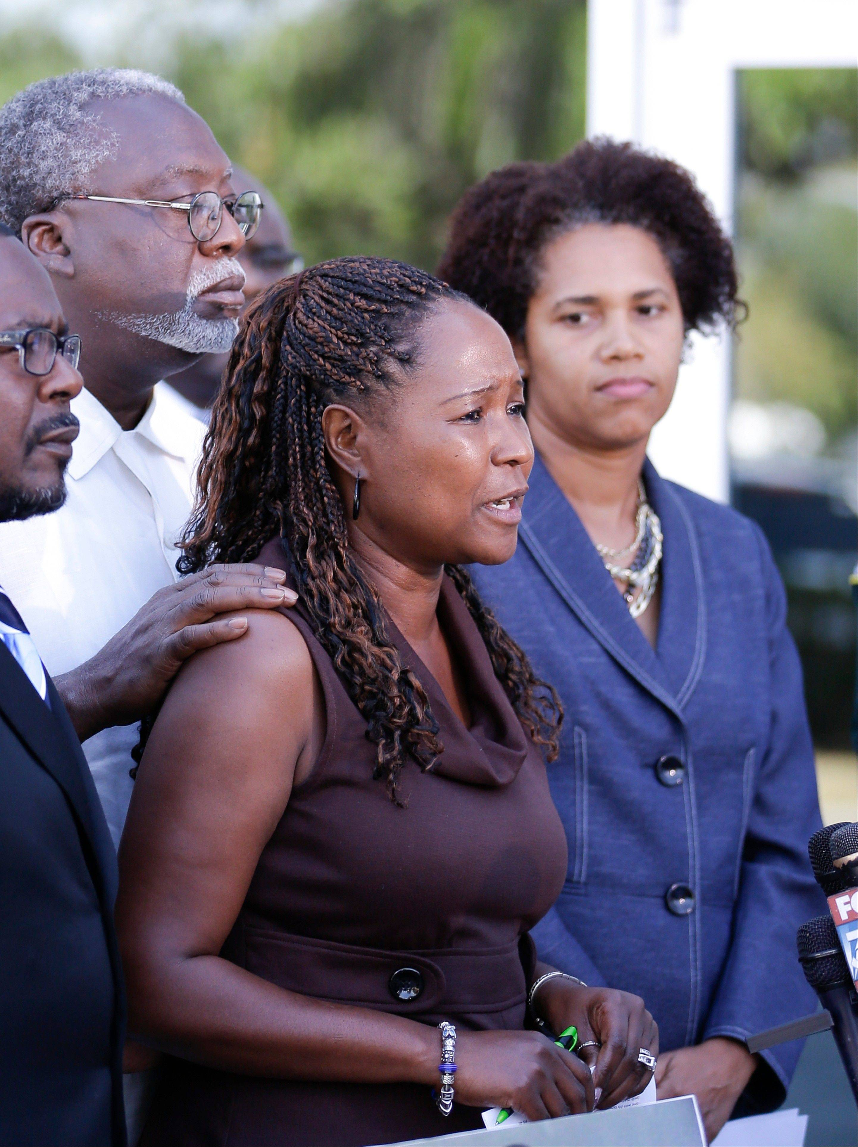 Lillie Danzy, center, mother of escaped inmate Charles Walker, with her husband Jeff Danzy, to her left, and attorney Rhonda Henderson, right, listen as she makes a plea Saturday for her son to turn himself in to authorities. The two men were later captured.