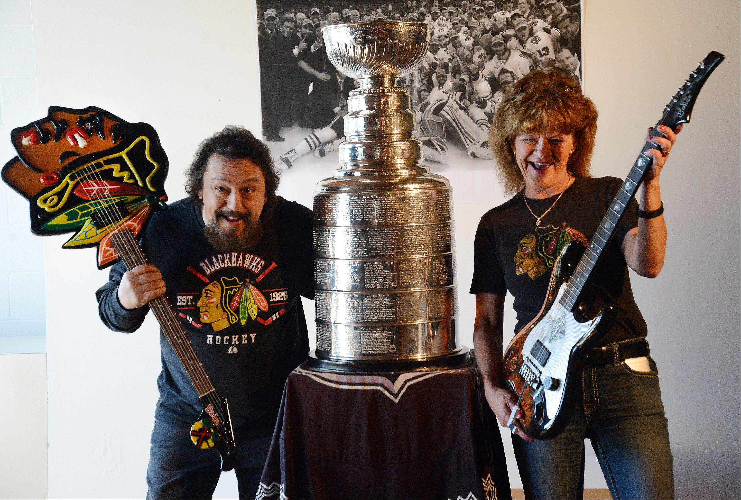 Rob and Beverly Bakes, of Bakes Guitars in Genoa, pose with their custom Blackhawks guitars with the Stanley Cup, which was on display at the Trickster Art Gallery in Schaumburg Saturday.