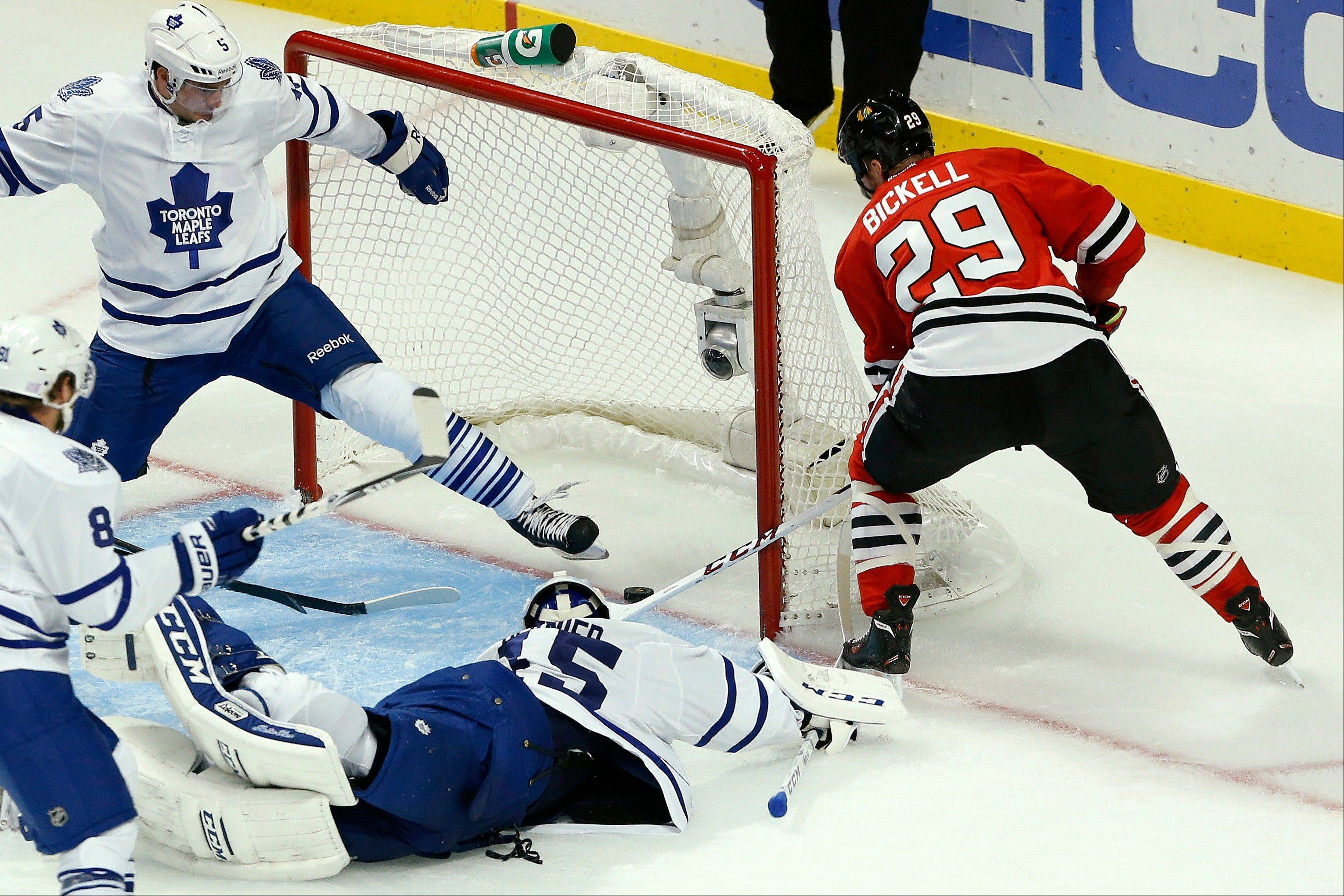 Blackhawks left wing Bryan Bickell (29) scores a goal past Toronto Maple Leafs goalie Jonathan Bernier (45) and defenseman Paul Ranger, top left, during the second period Saturday in Chicago.