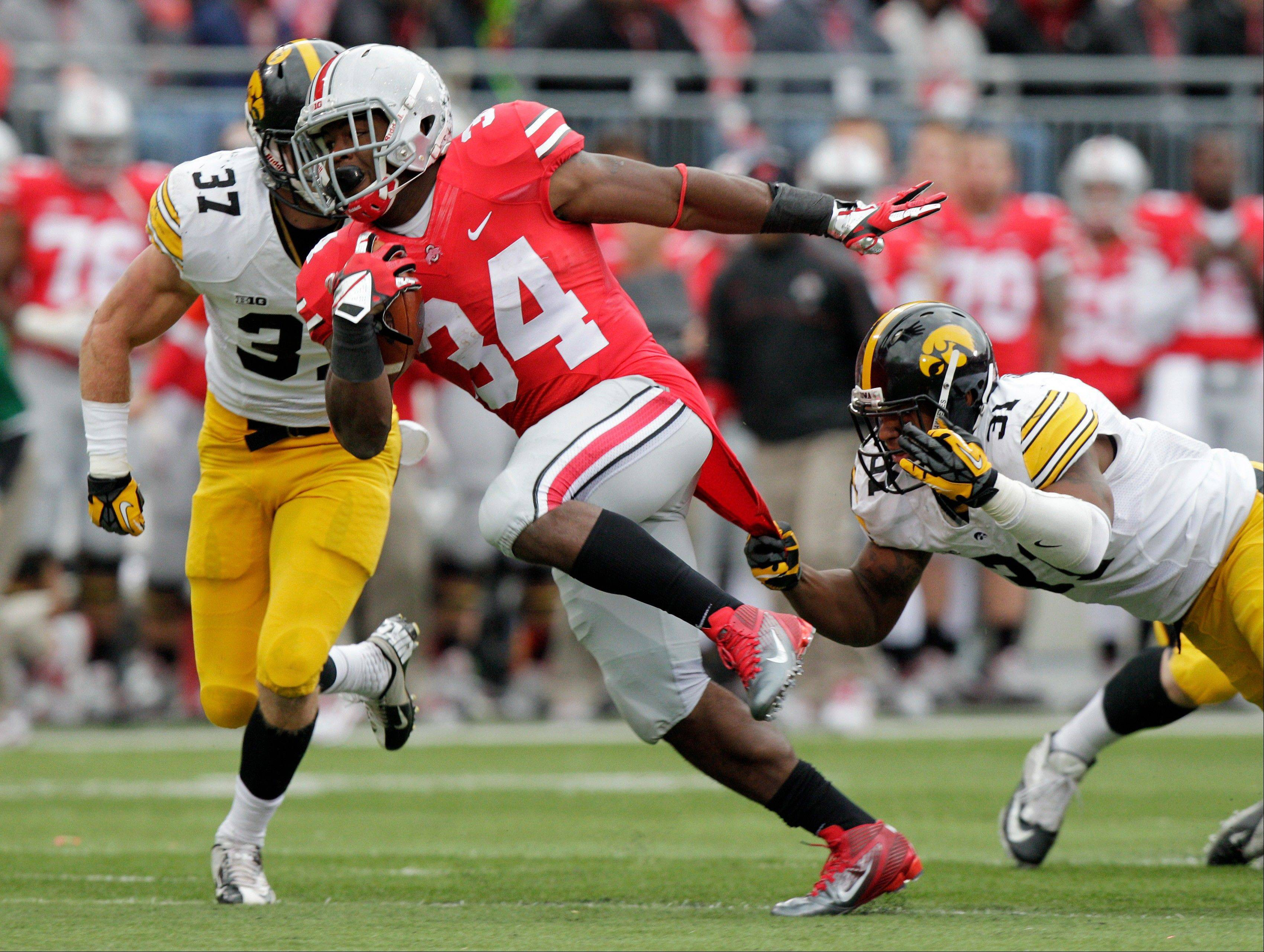 Ohio State running back Carlos Hyde, center, crosses the line of scrimmage between Iowa defenders John Lowdermilk, left, and Anthony Hitchens during the second quarter.